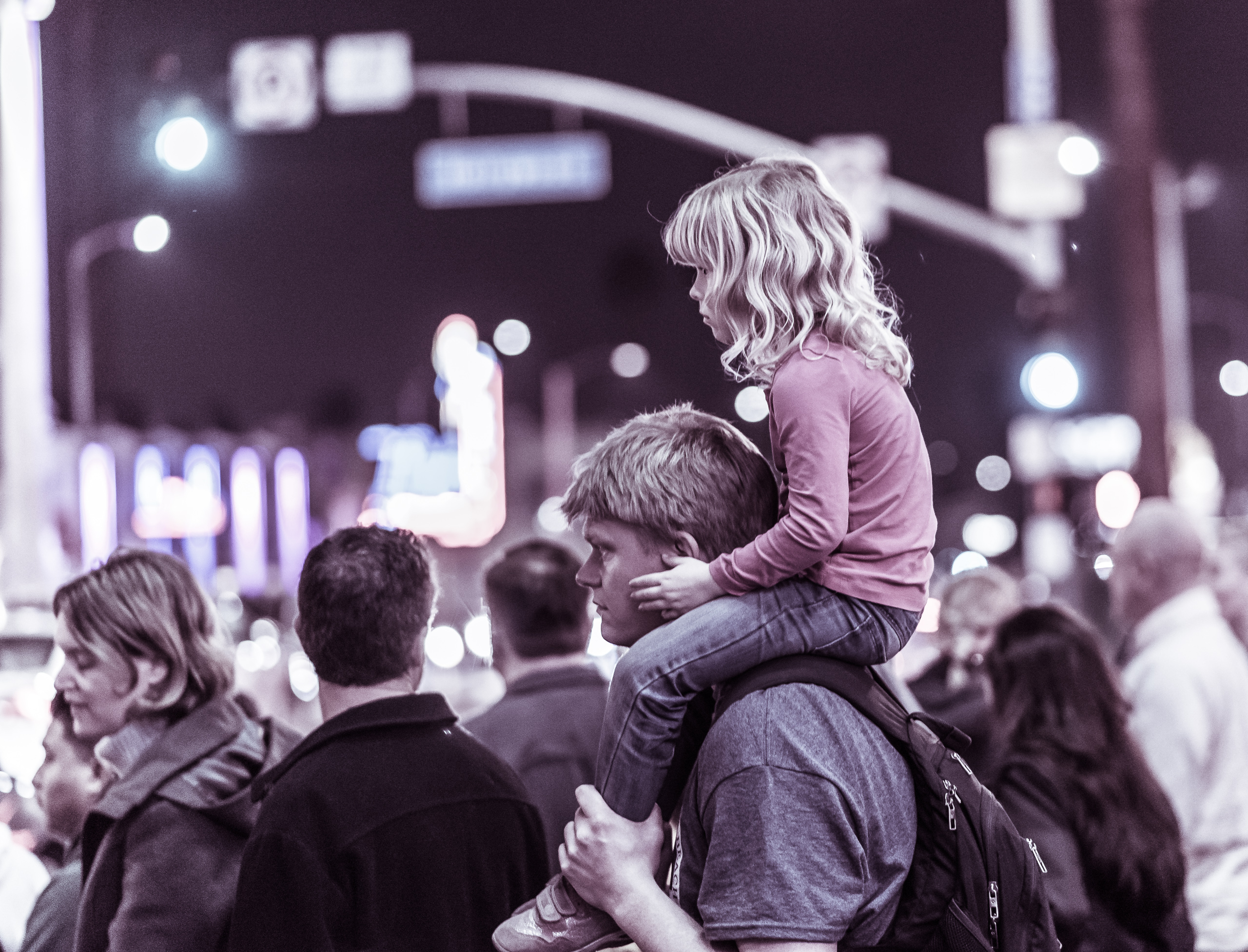 a young girl rides on her father's shoulders with her hands on his cheeks