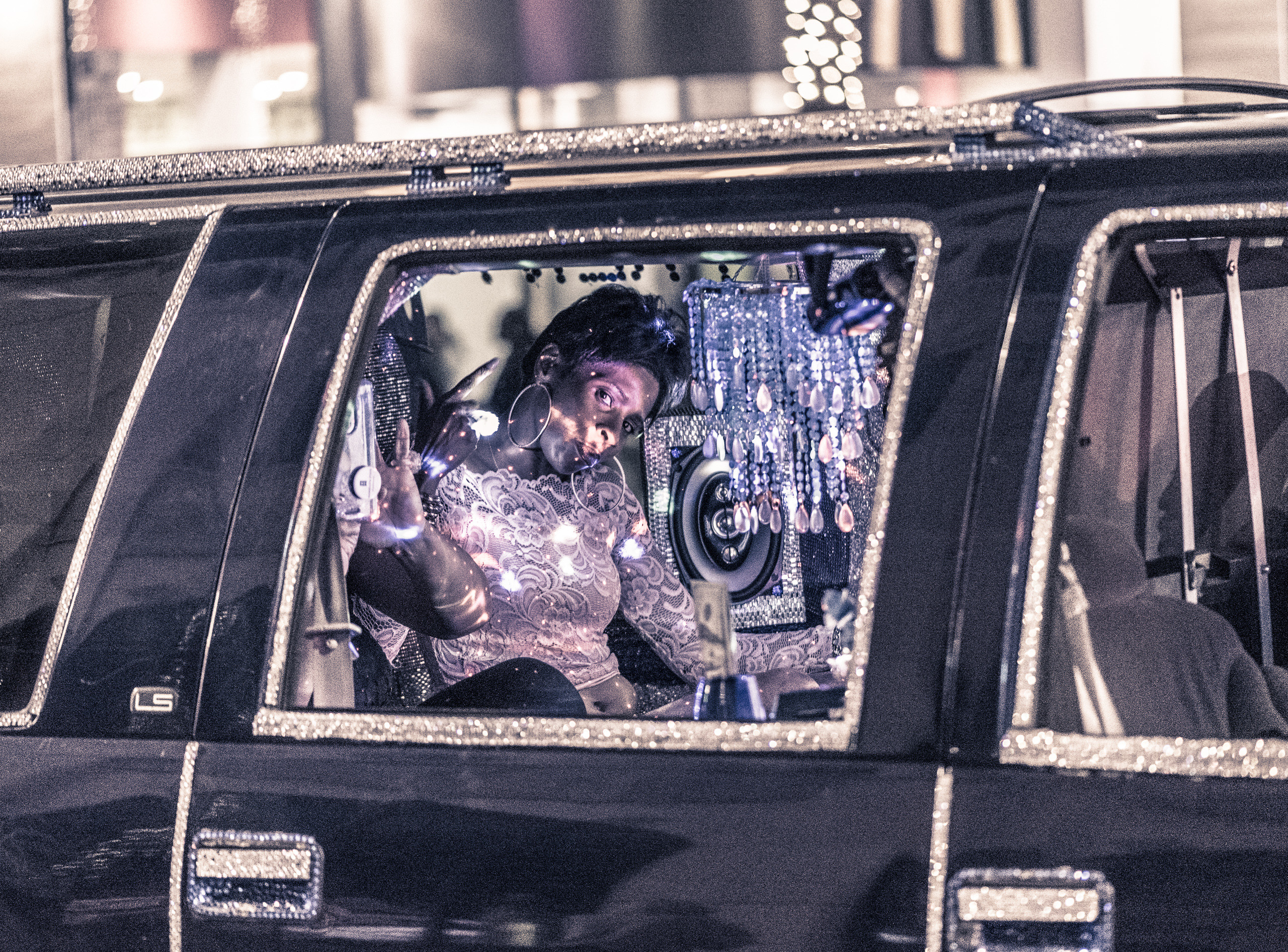 an elegant woman rides in a sparkling, bedazzled limo