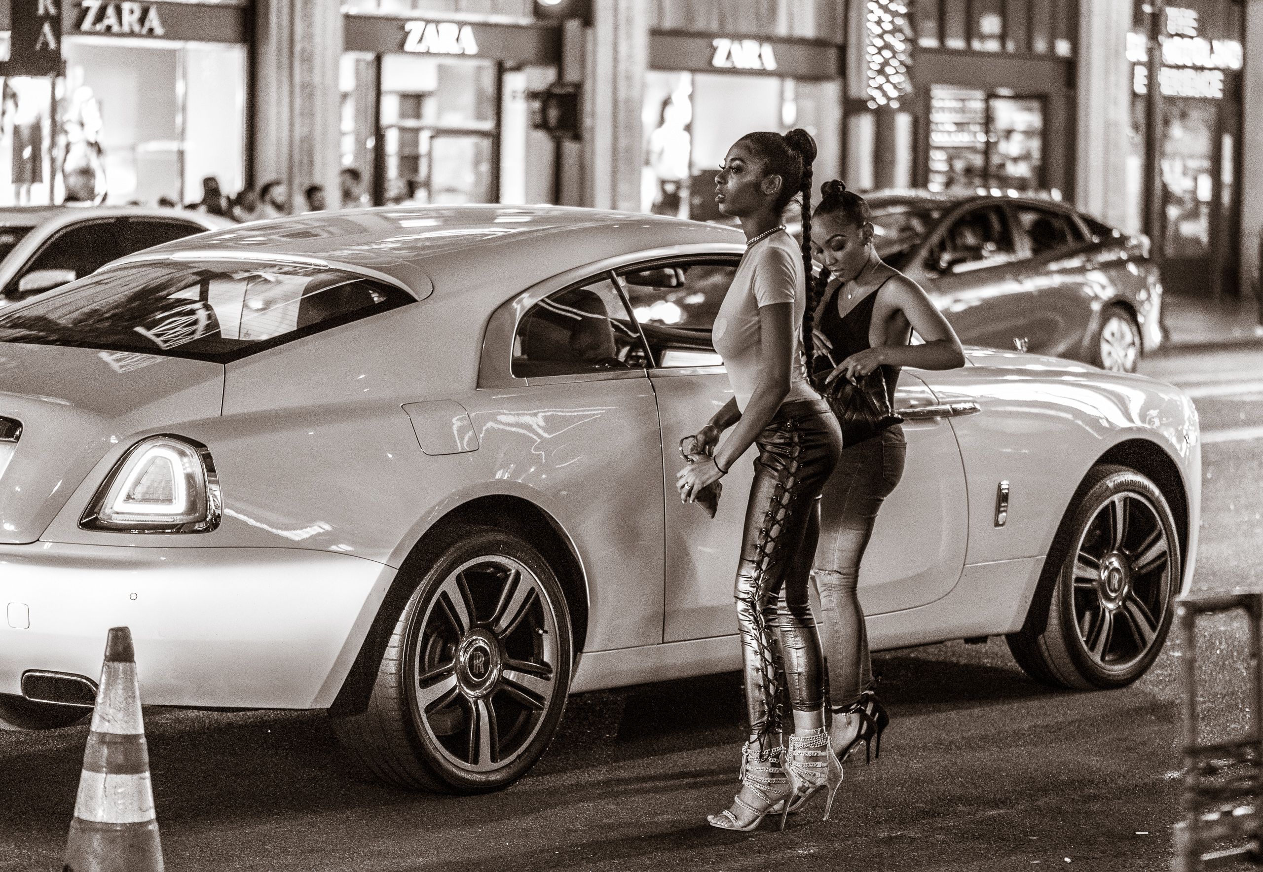 two women stand in the street, about to enter a Uber ride