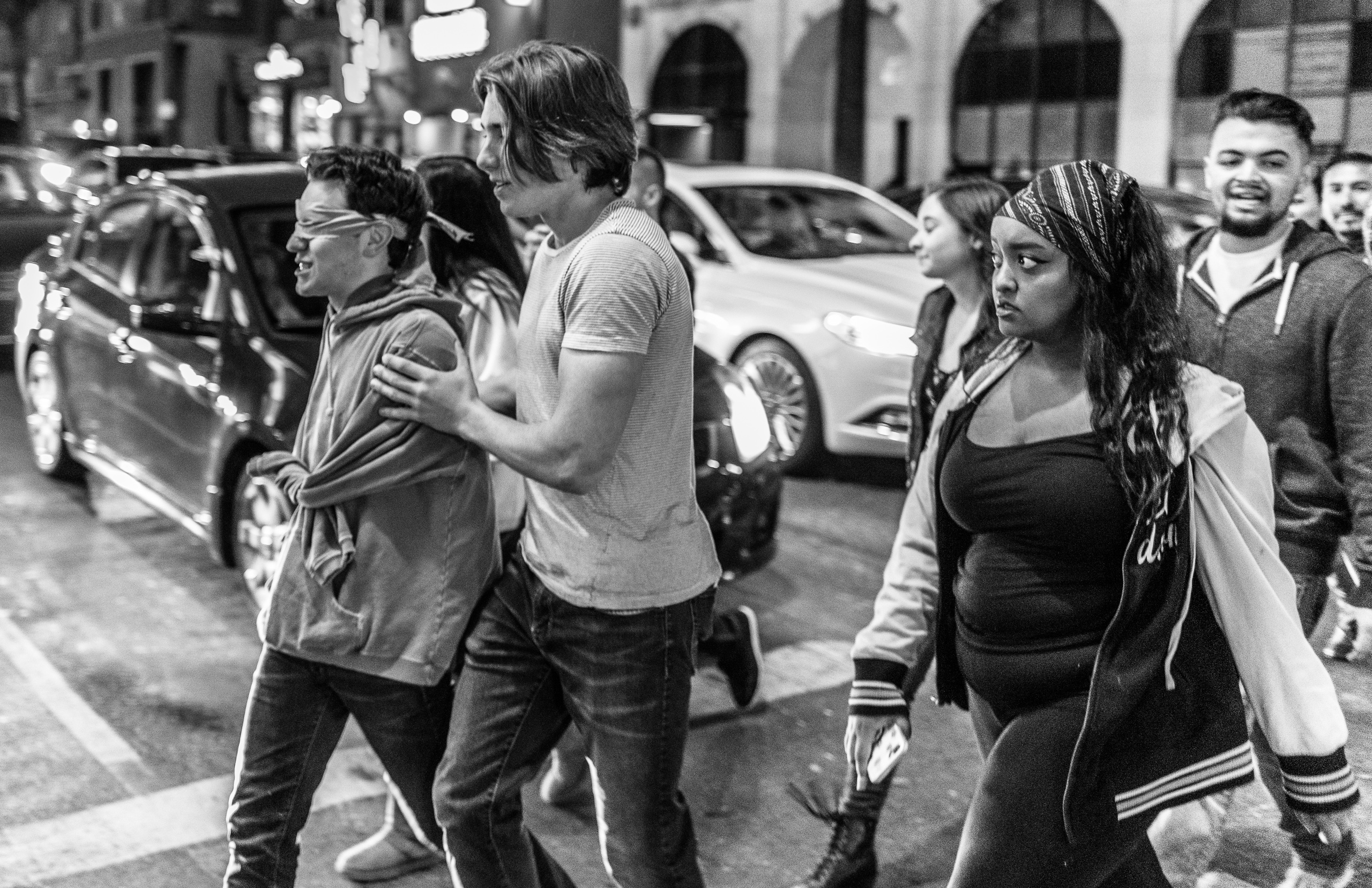 a young, blindfolded guy is escorted across the street as other pedestrians look on