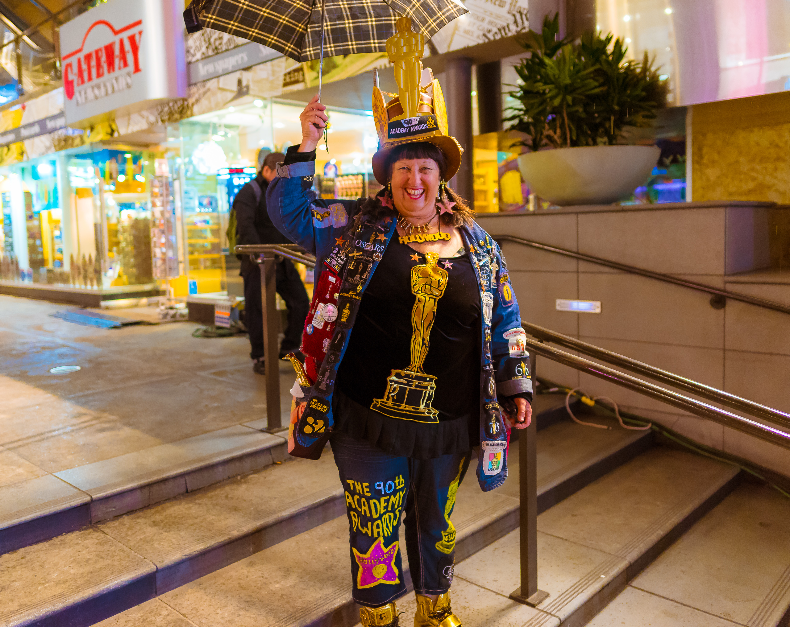 """A woman stands on the steps at the Hollywood & Highland center wearing an """"Oscar outfit"""" composed of many Academy Awards elements, like stars and Oscar statuettes."""