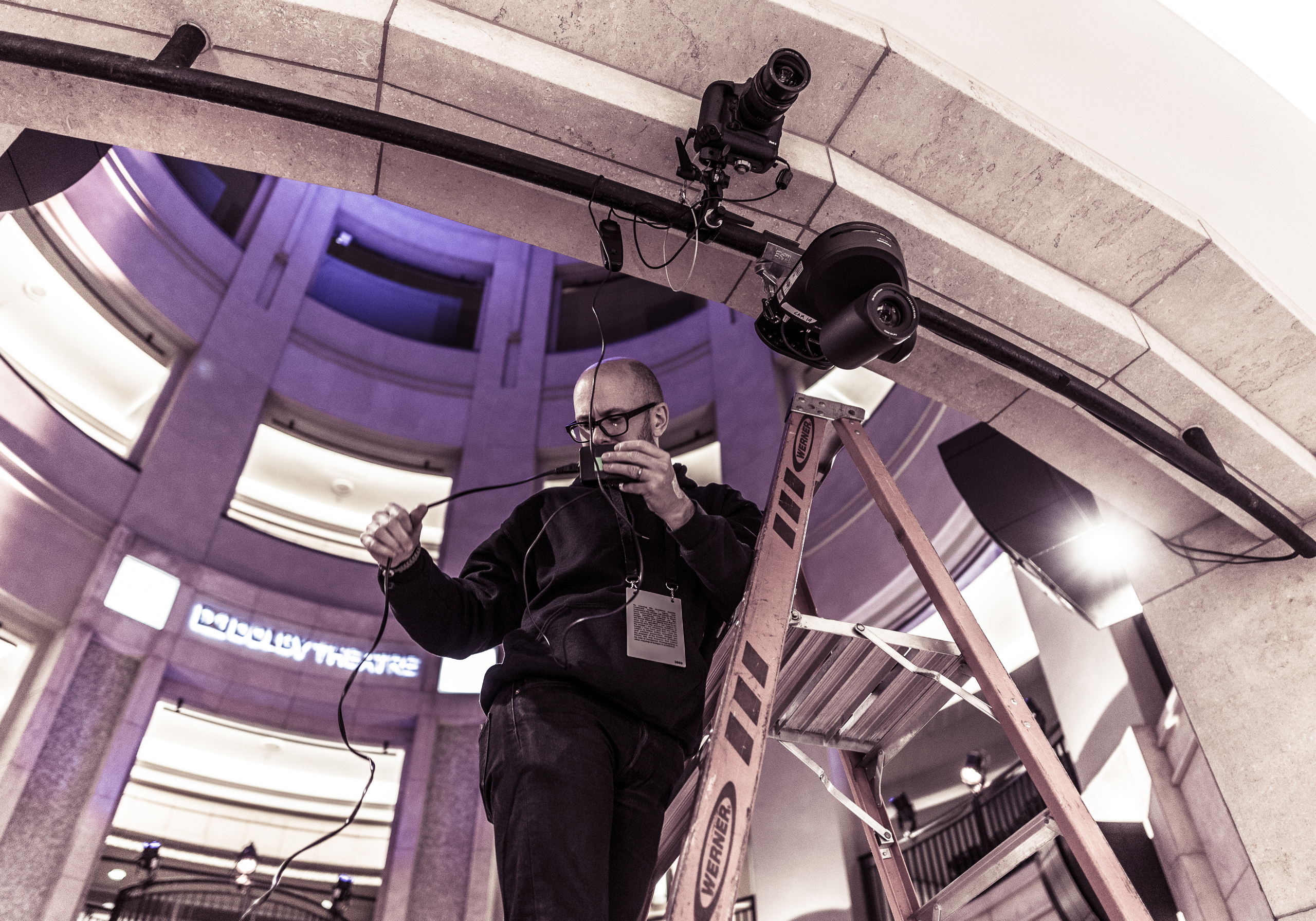 a man rigs a remote camera at the top of the stairway to the Dolby Theatre
