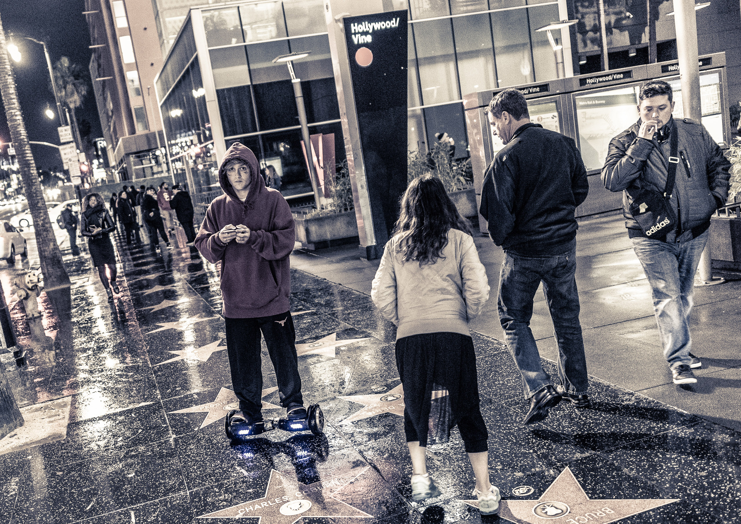 a guy in a red hoodie rides a hoverboard down the Hollywood Blvd sidewalk in front of the Hollywood & Vine Metro station. The sidewalk is wet from a light rain a few moments earlier. Other pedestrians walk in either direction or stop to read the names of the stars on the sidewalk