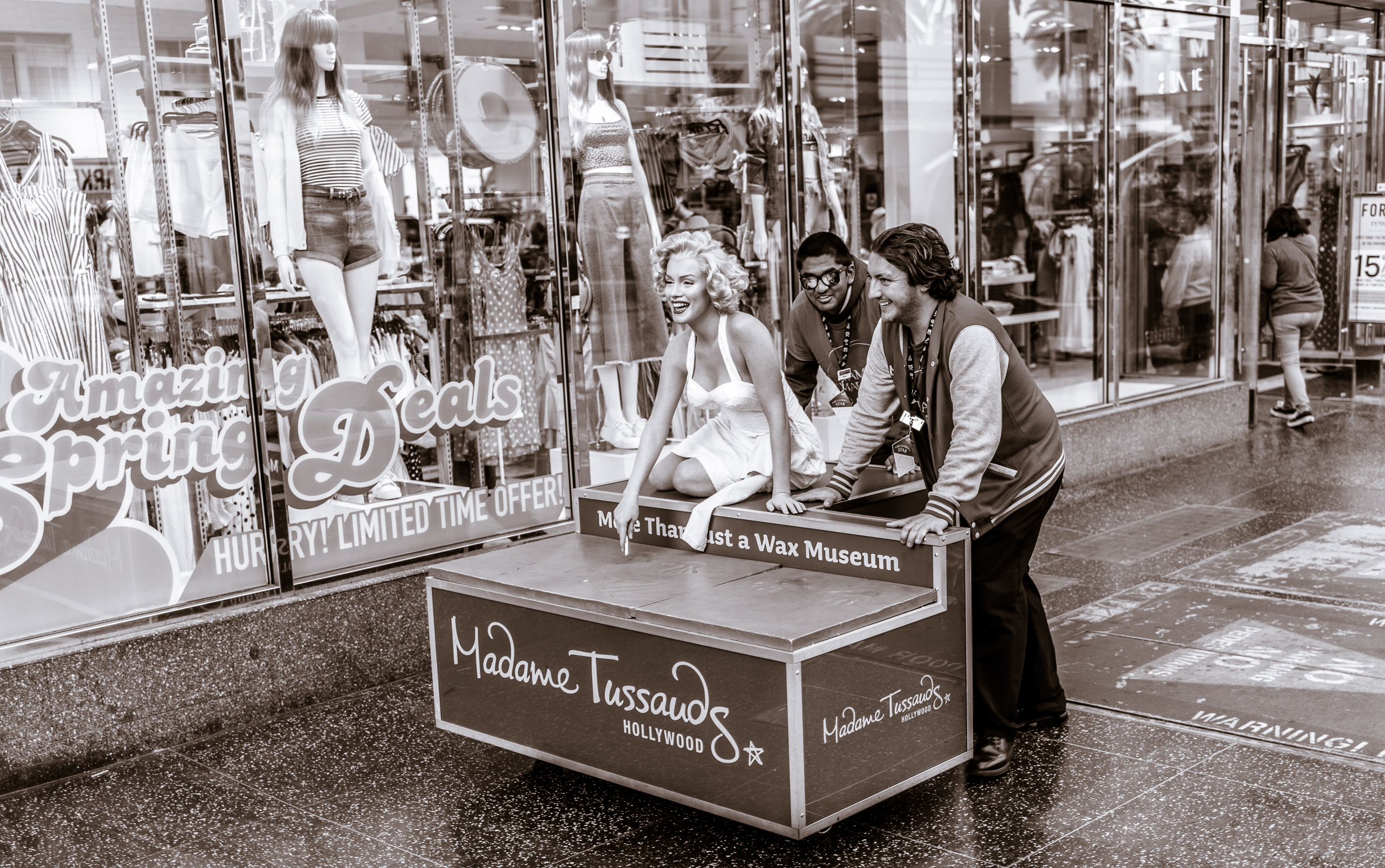 2 employees from Madame Tussauds Hollywood wheel a wax sculpture of Marilyn Monroe down Hollywood Blvd. From Marilyn's display spot at the Hollywood & Highland Metro Red Line exit, they wheel her west about a block to the Madame Tussauds building.