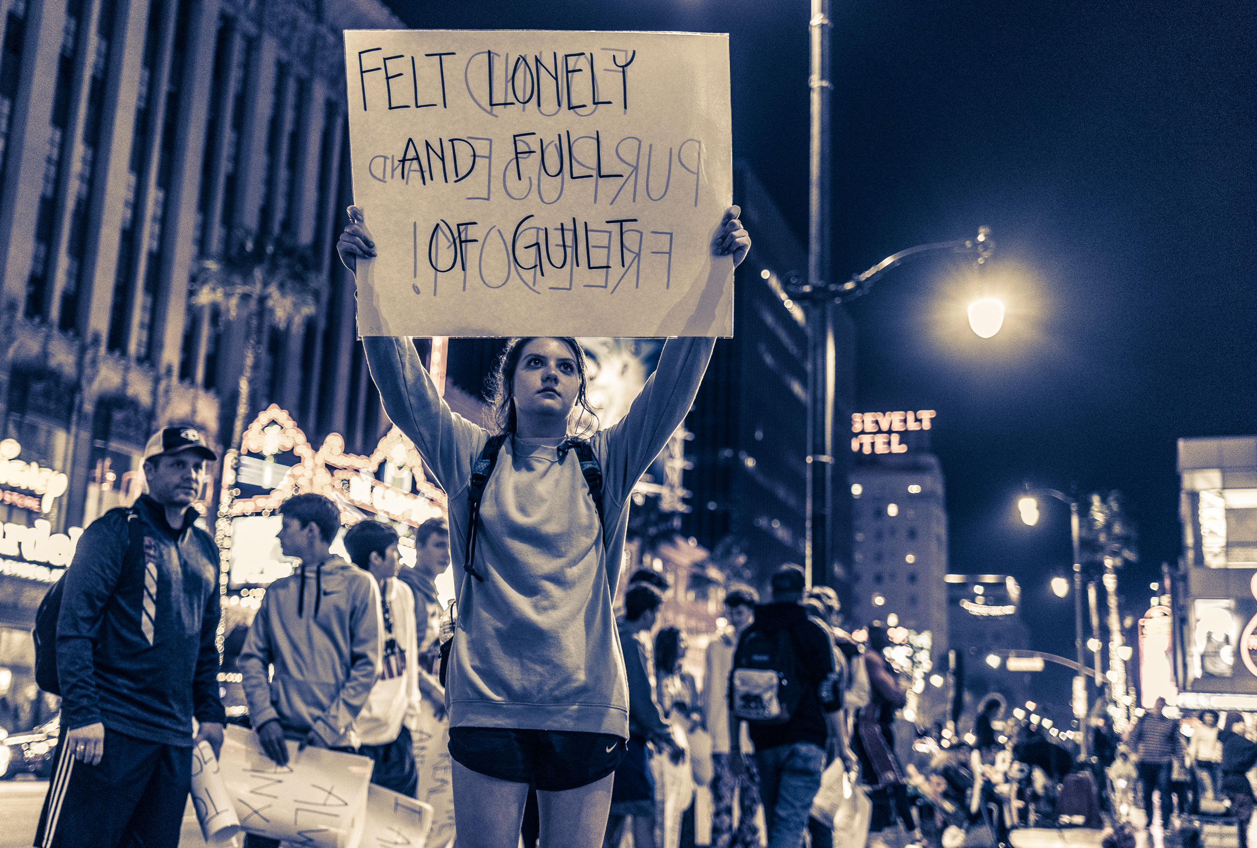 """a high school student from Texas holds a large sign over her head on Hollywood Blvd in Los Angeles. Her sign reads """"felt lonely and full of guilt"""""""