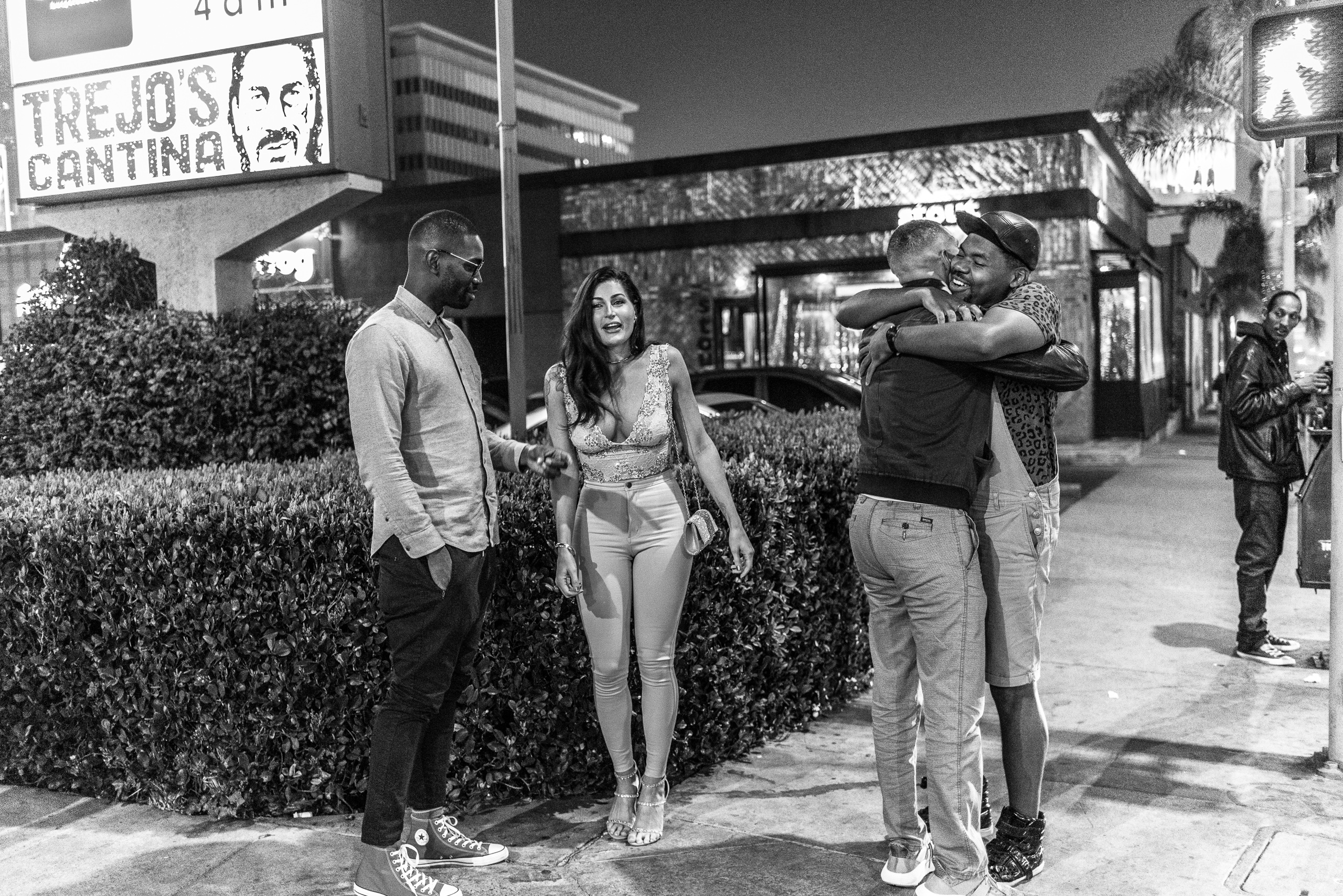 4 friends talk and hug on a Hollywood street corner