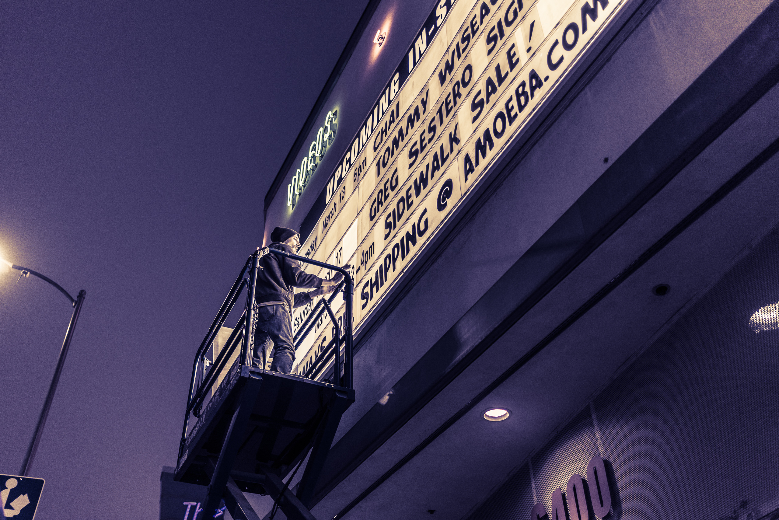 a man on a scissors-lift changes the upcoming events on the marquee outside Amoeba Music Hollywood on Sunset Blvd.