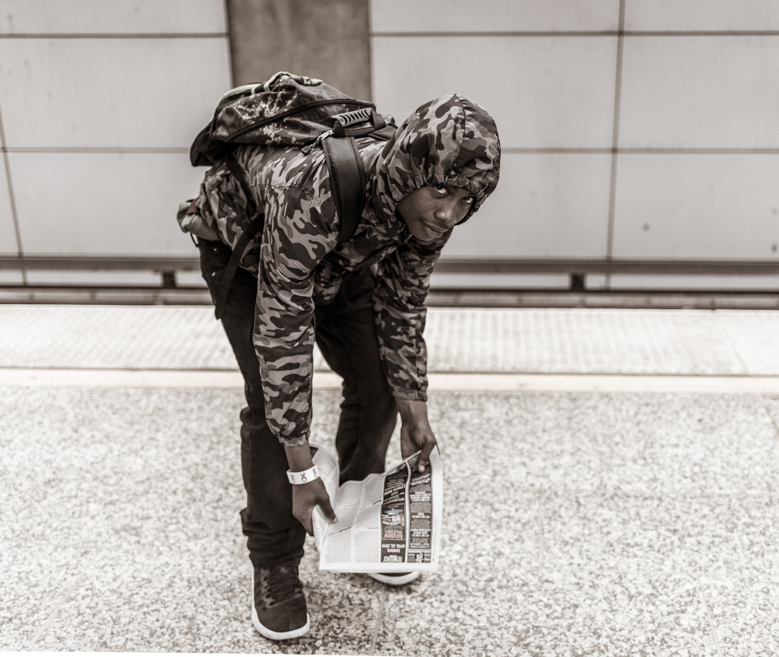 a young man bends over in a portrait pose while he waits for the Red Line train at the Hollywood & Highland platform