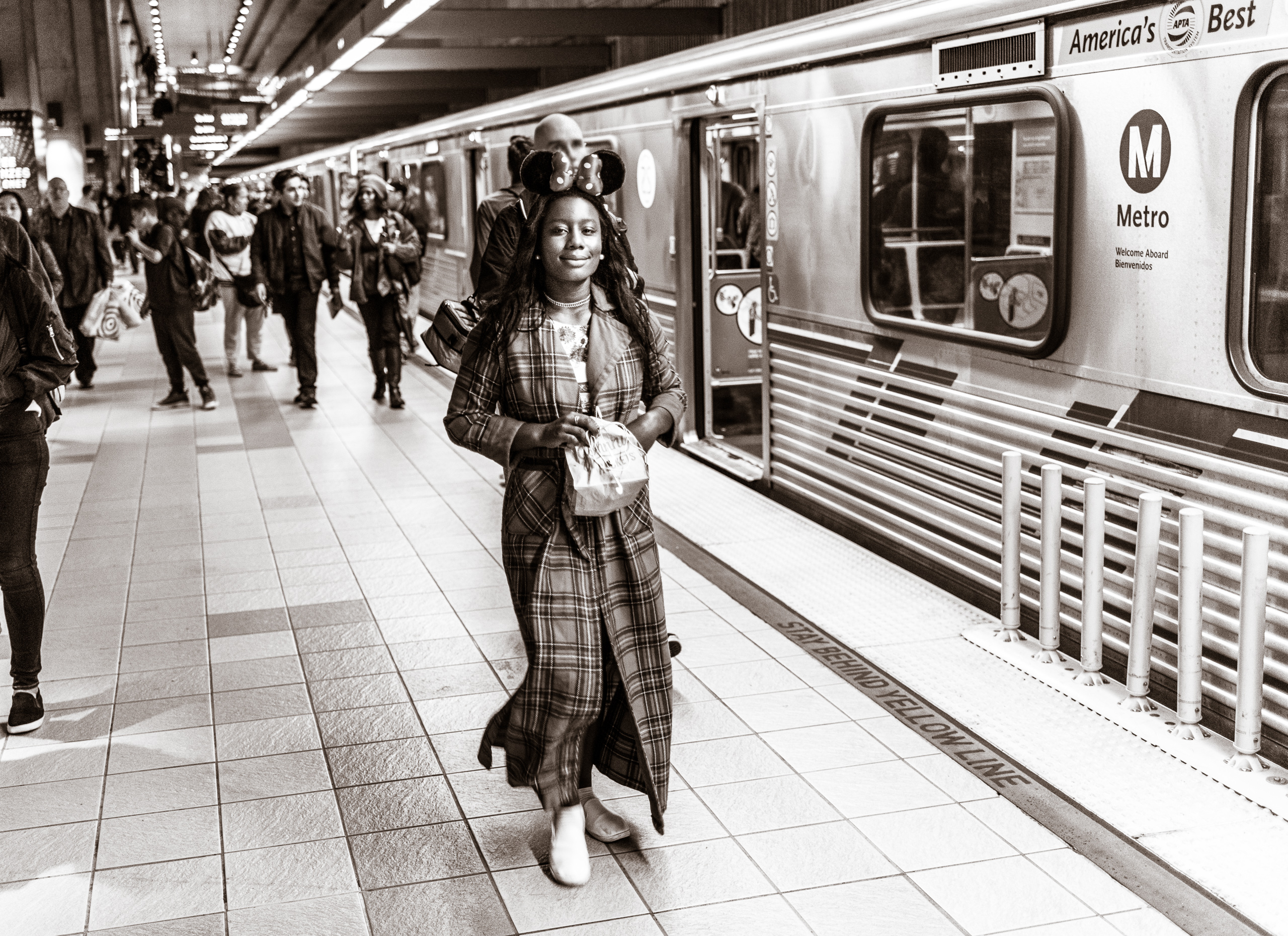 a young woman in a long coat walks across the platform wearing a pair of Minnie Mouse ears
