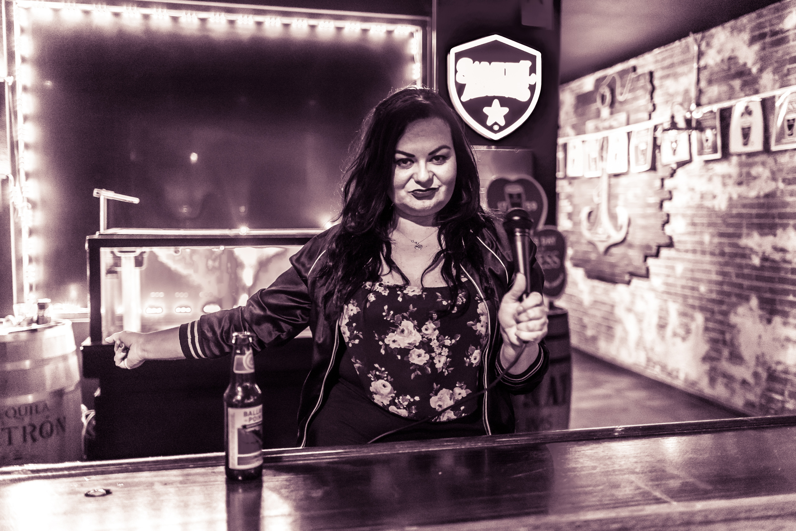 A woman in the window of a bar on Hollywood Blvd with a microphone and inviting pedestrians into the bar