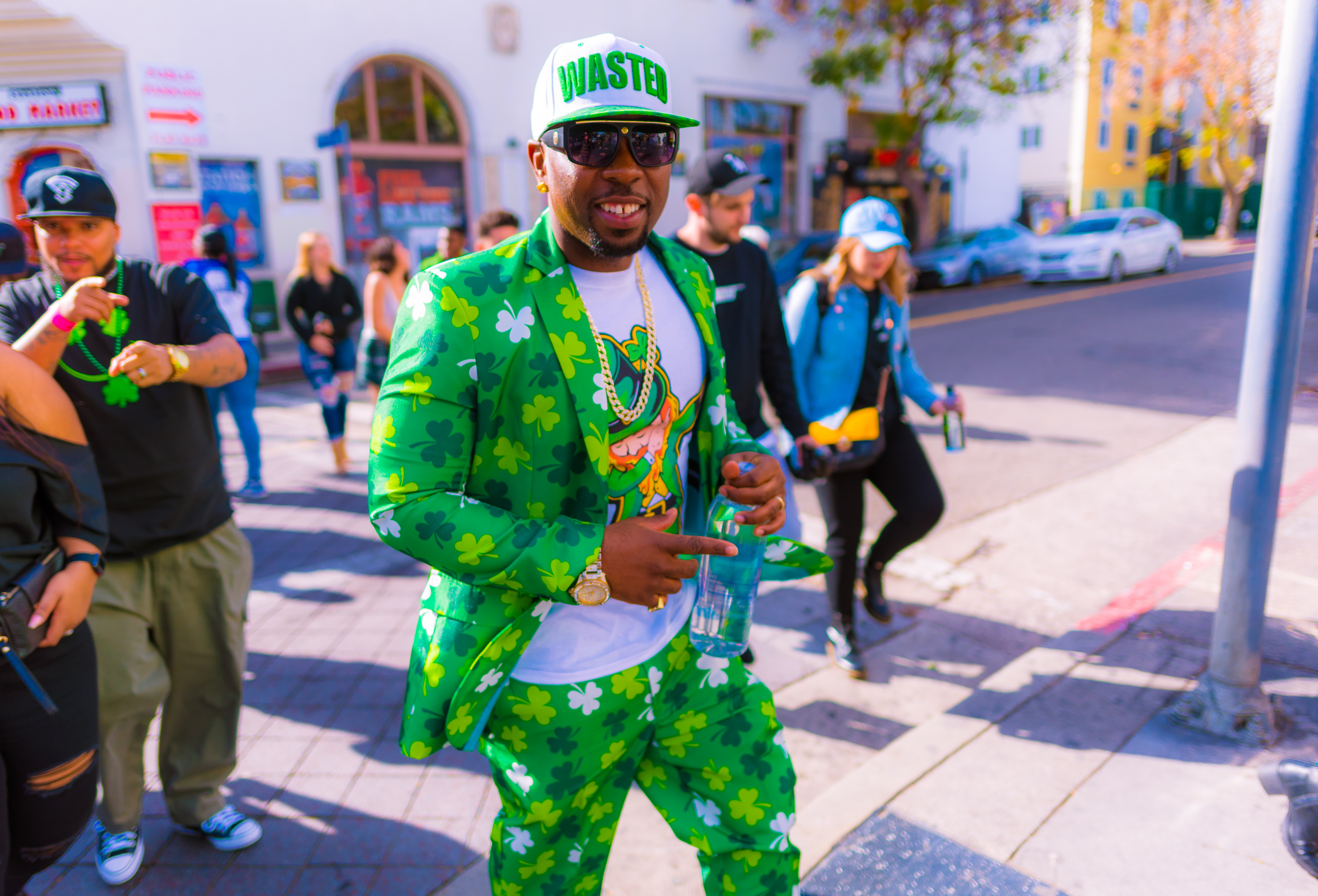 """A guy walking down Hollywood Blvd in a green shamrock suit and wearing a baseball cap that reads """"wasted"""""""