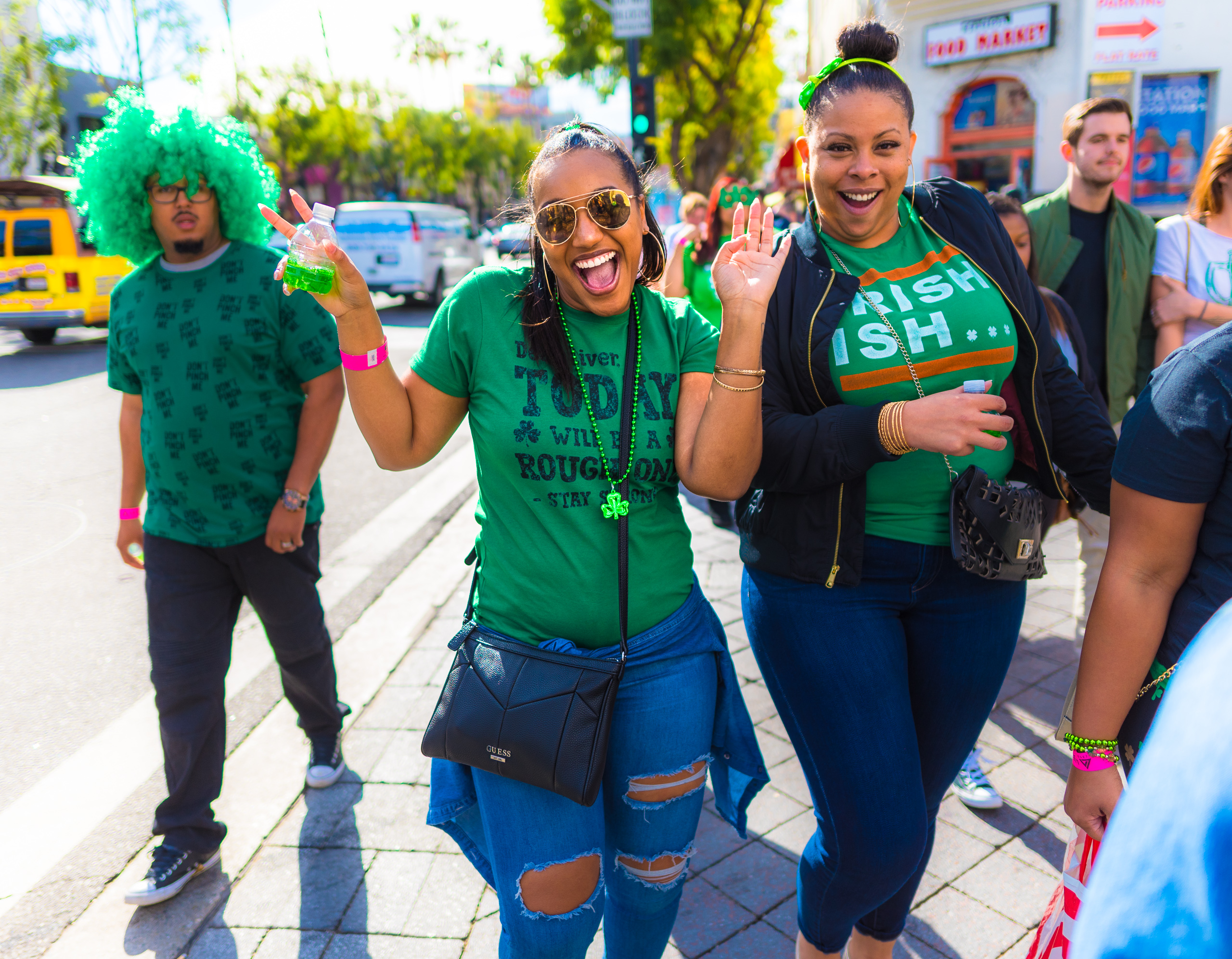 A woman in a green t-shirt and torn blue jeans walks down Hollywood Blvd on Saint Patrick's Day. She holds a bottle with green liquid in one hand, and makes peace signs with both hands. She looks at the camera with a huge smile. Friends also in green walk on either side of her.
