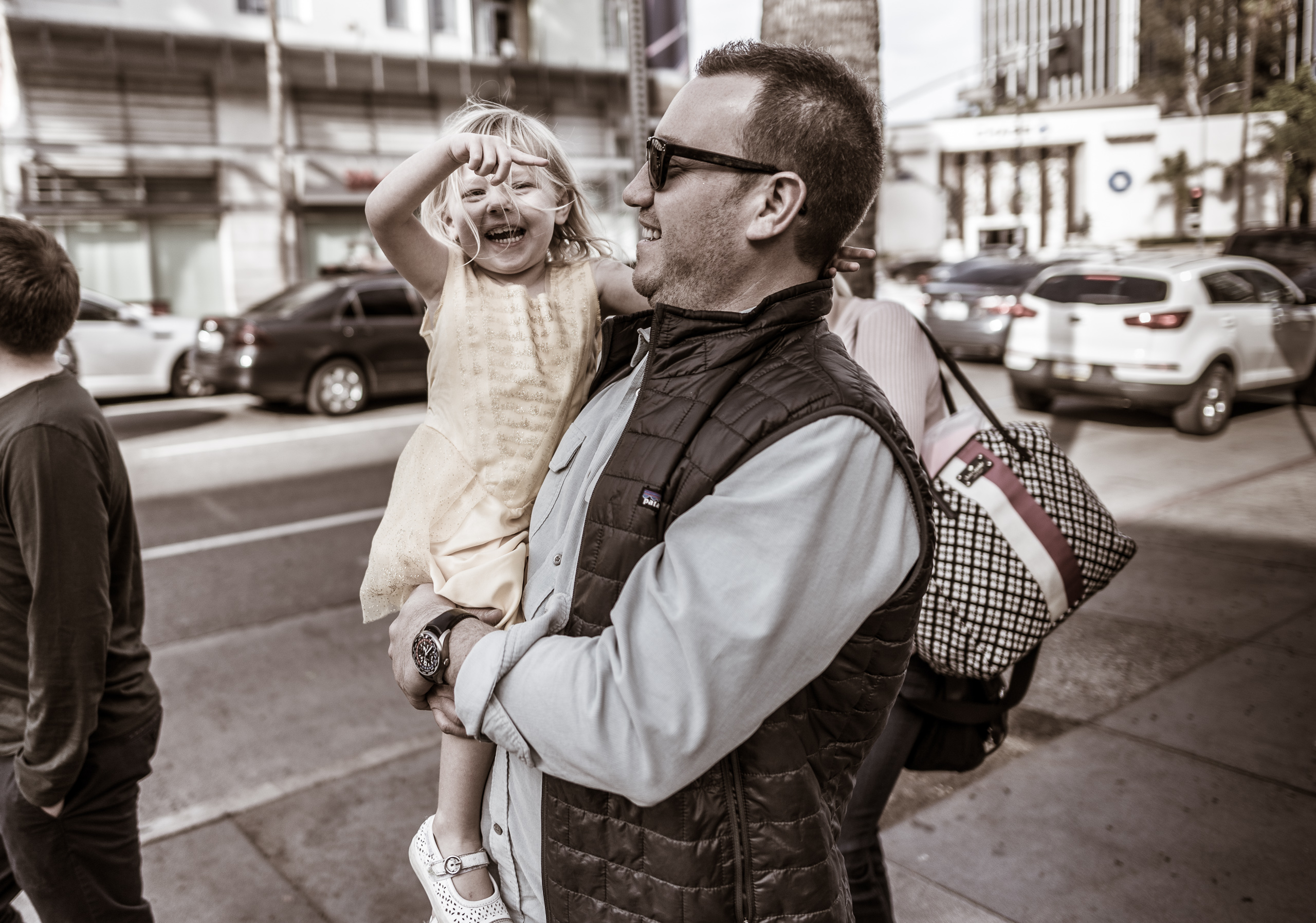a man in sunglasses carries his young daughter in a yellow dress as she gaily points out a direction