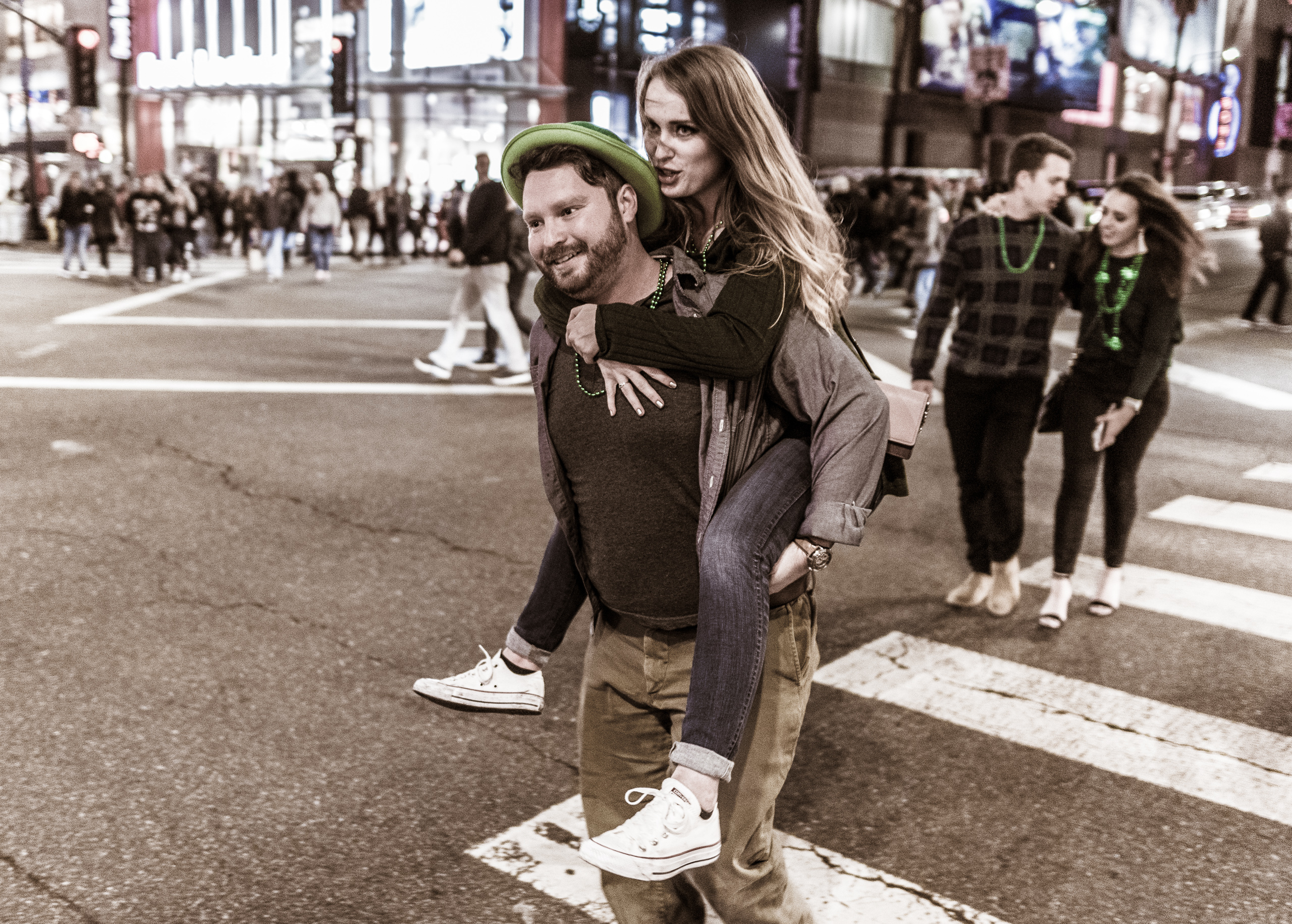 a man carries a woman on his back as they cross Hollywood Blvd on St. Patrick's Day night. He wears a green hat and they both wear green beads. Behind them another couple crosses the street, also wearing green beads around their neck.