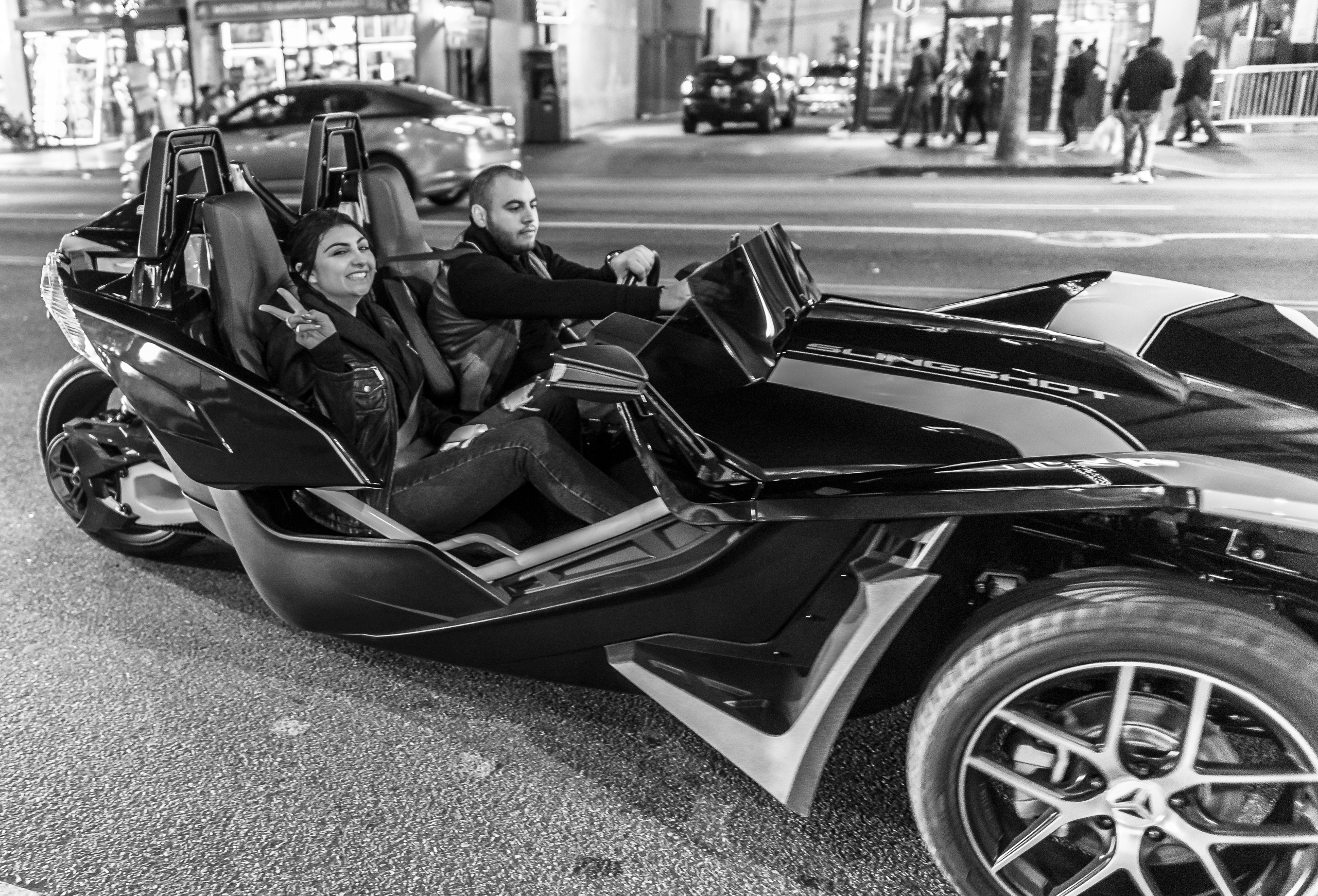 a man drives a Polaris Slingshot down Hollwyood Blvd on a Saturday night. In the passenger seat a woman smiles at my camera and makes a peace sign