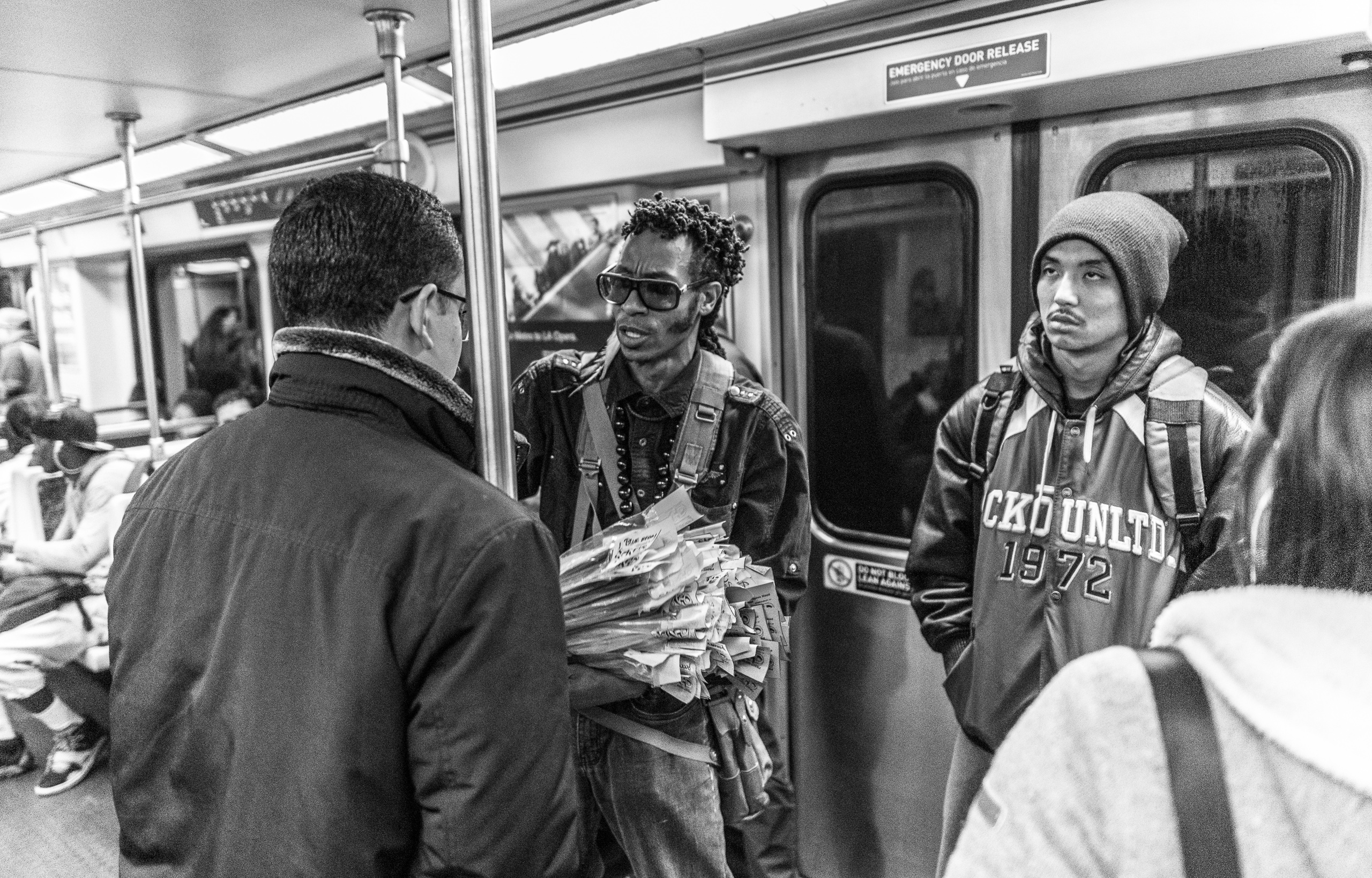 a man sells a package of incense to another man in a Los Angeles' Metro Red Line train car
