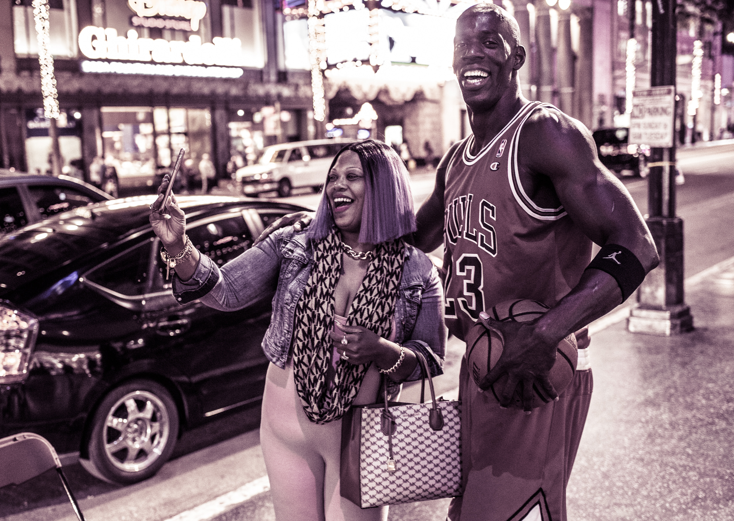 A woman with a black-and-lavender ombre takes a selfie with a Michael Jordan character on Hollywood Blvd.