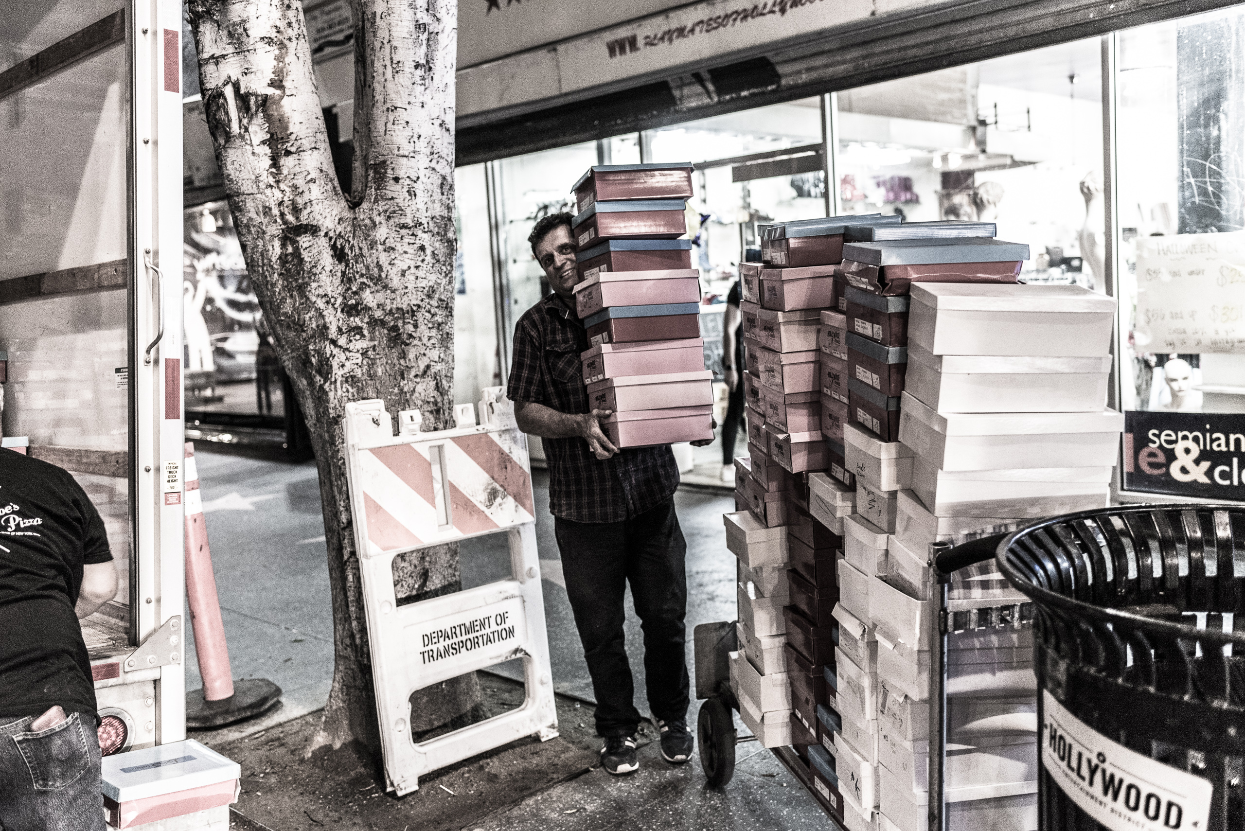 a guy carries a 10-foot-tall stack of shoe boxes out of the Playmates store at 6438 Hollywood Blvd, Hollywood 90028, and loads them into a moving van.