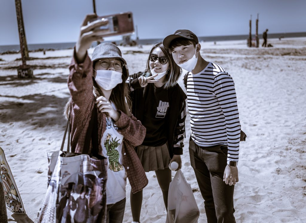 three students take a selfie after having painted at the Art Walls at Venice Beach, CA