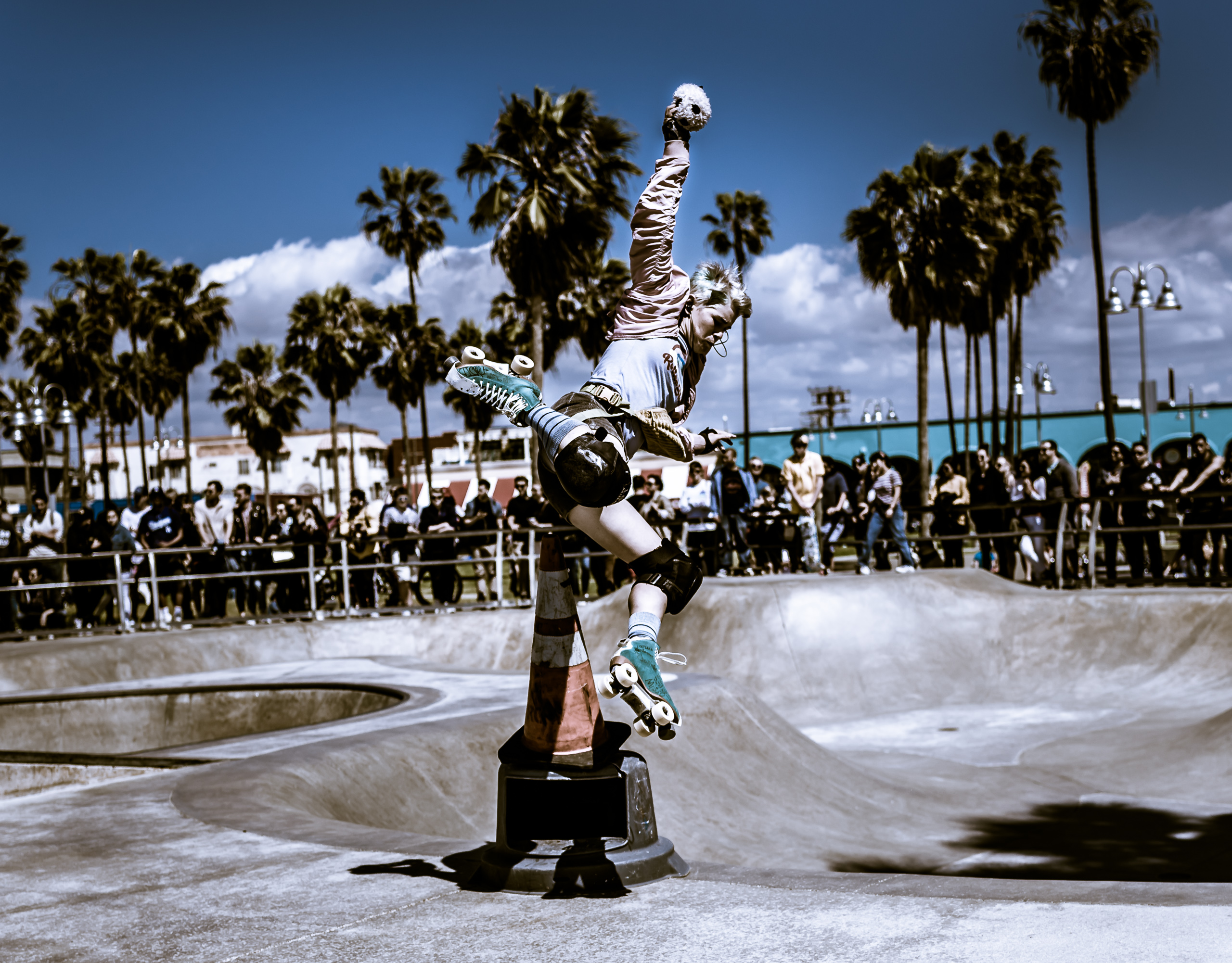 a woman in a pink jacket, short pants, knee pads, and green quad roller skates jumps over a tall cone at the Venice Beach Skate Park in Venice Beach California
