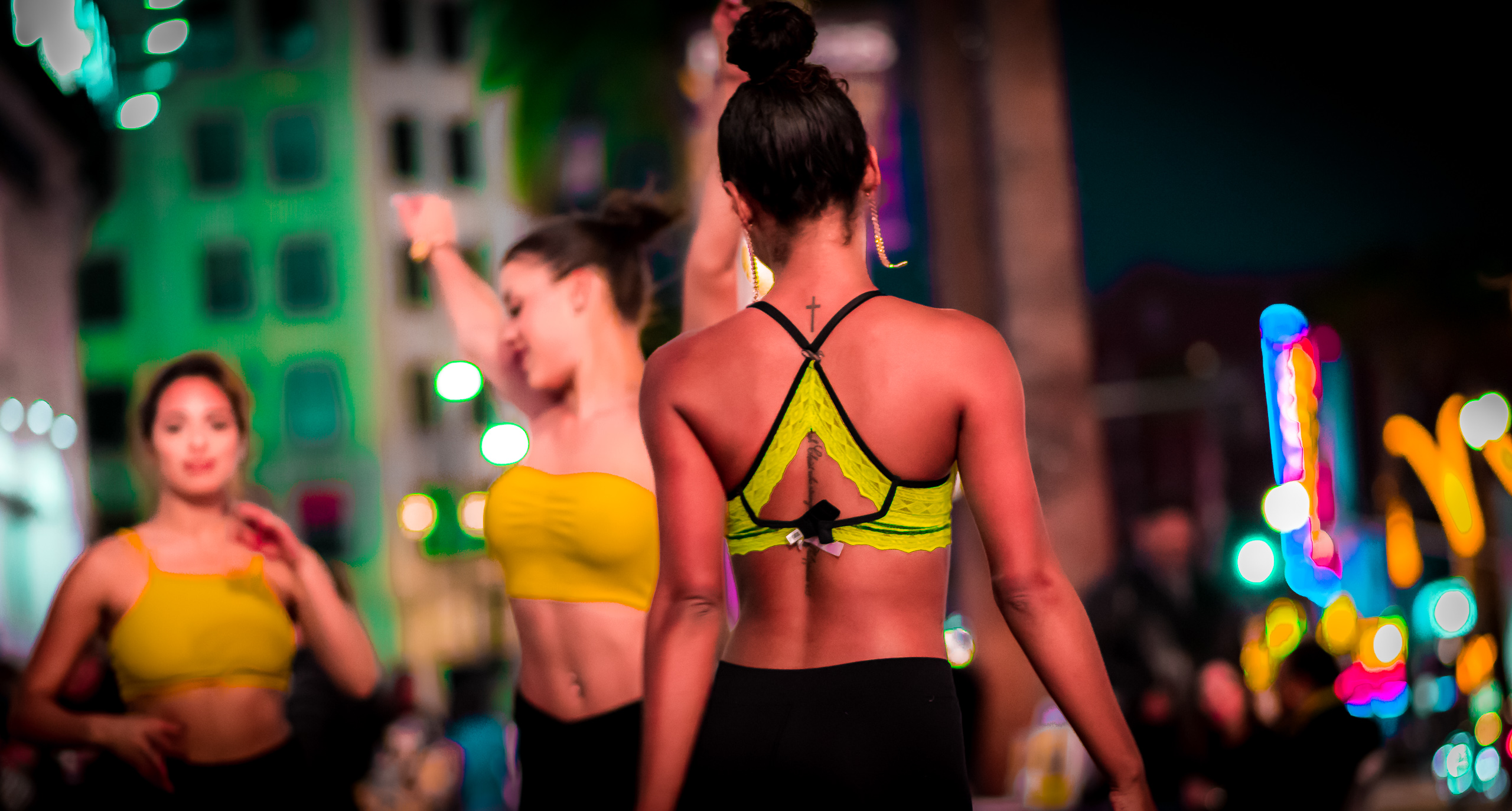 Dancers in green and yellow tops and black pants perform for a dance video on Hollywood Blvd.