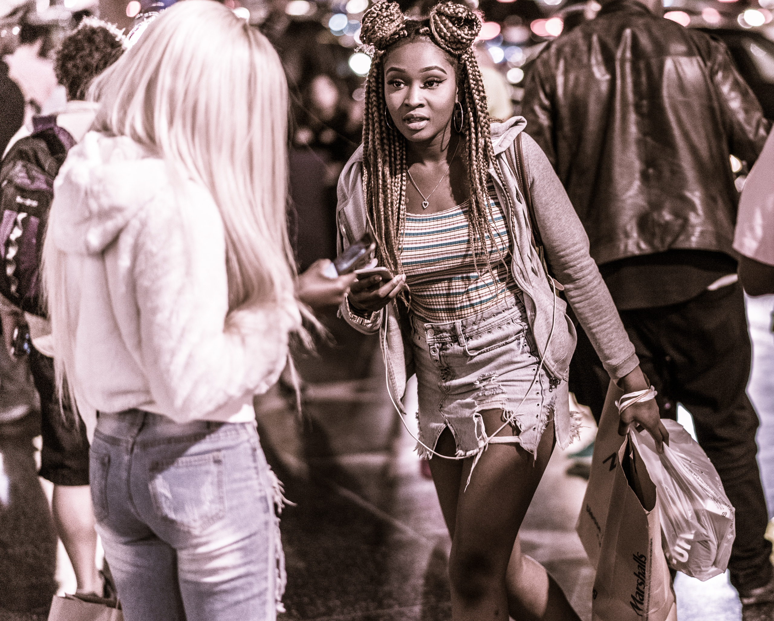 a woman with heavily braided hair walks down Hollywood Blvd.