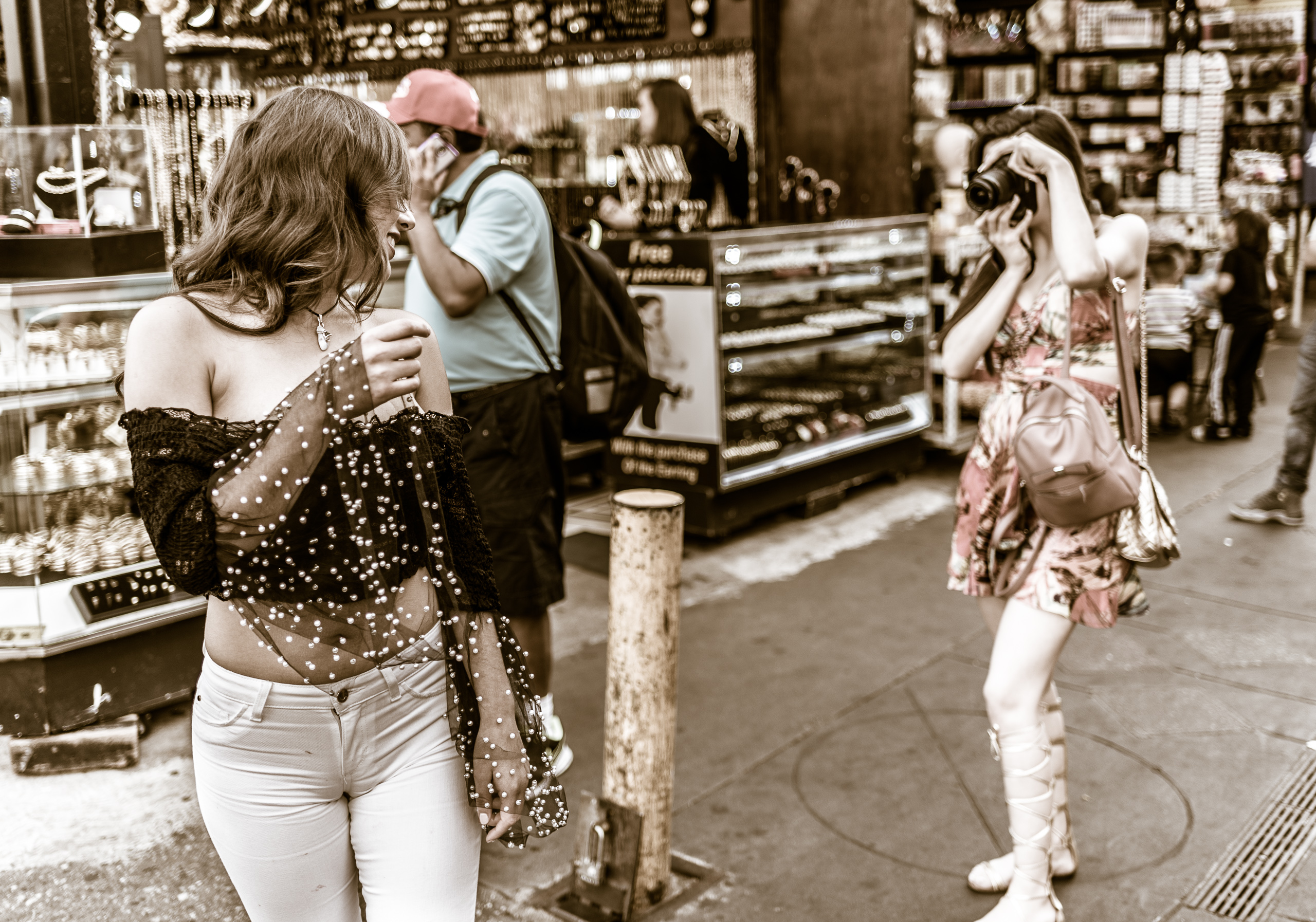 Two friends in Santee Alley. One turns to pose for the other who holds a camera.