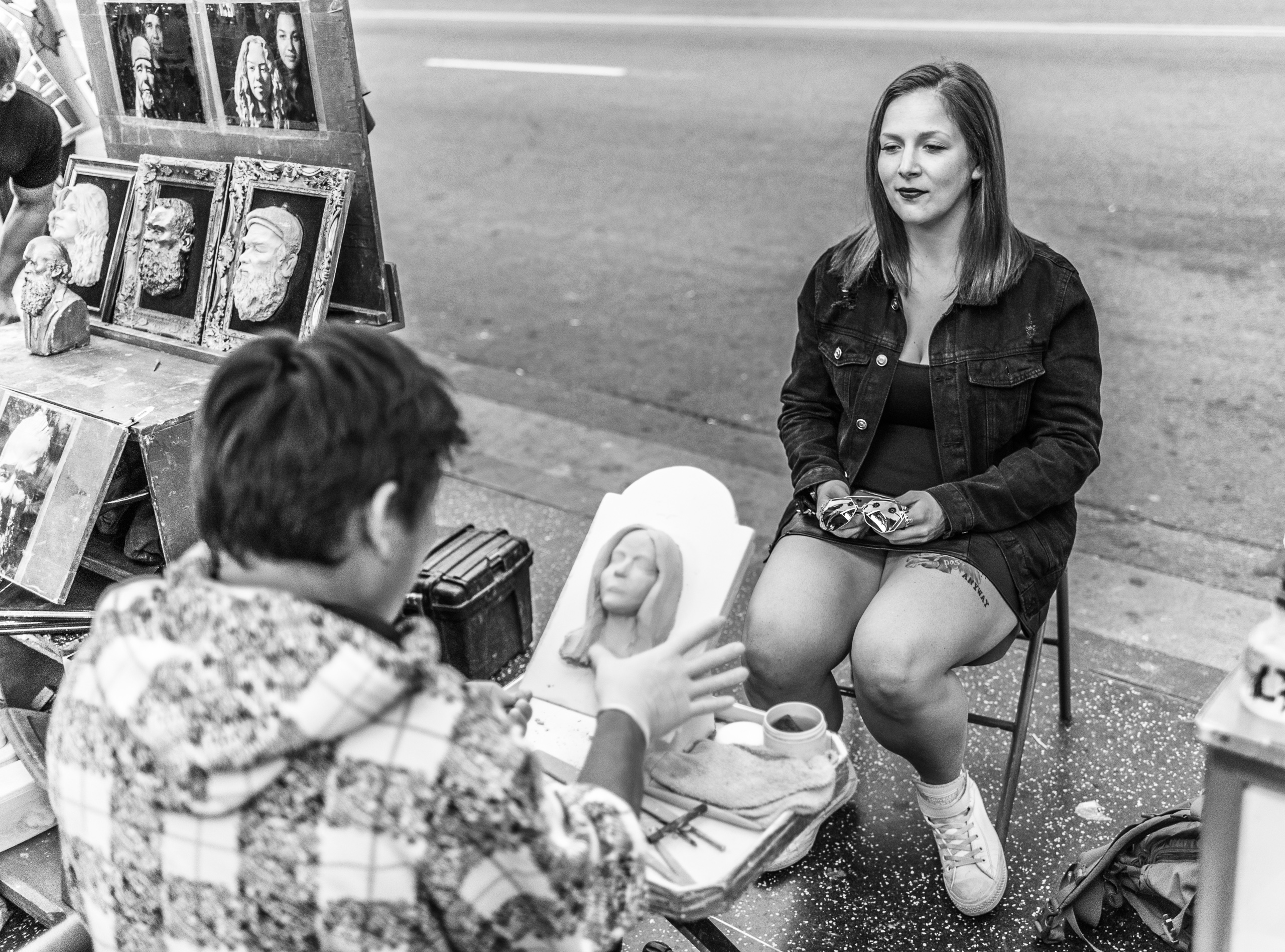 a woman sits in a chair on Hollywood Blvd as a man sculpts a small likeness of her face