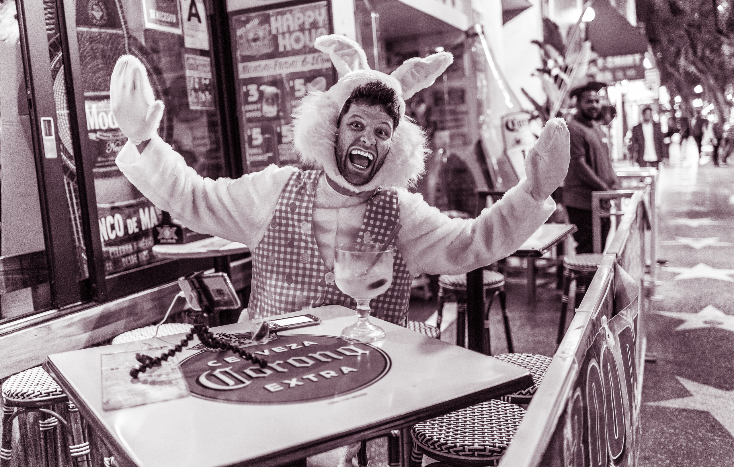 "a guy in a full bunny suit sits at a table at a sidewalk bar on Hollywood Blvd. His arms are outstretched and he gives a huge smile to the camera. He also has a phone on a gorillapod pointed at himself.  The table he sits at has a big circular logo on it with the words ""Cerveza Corona Extra"""