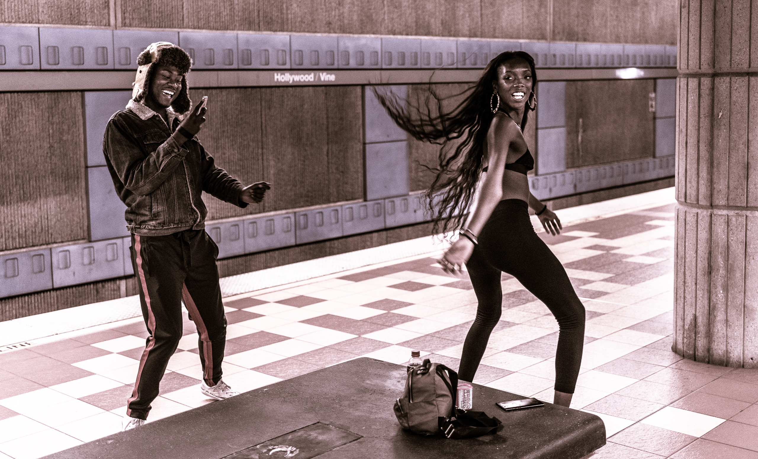 A girl dances with joy as her long black hair flows behind her. A guy also sways as he holds a cell phone to play music and take her picture. Metro Red Line platform at Hollywood & Vine, in Hollywood, Los Angeles, CA