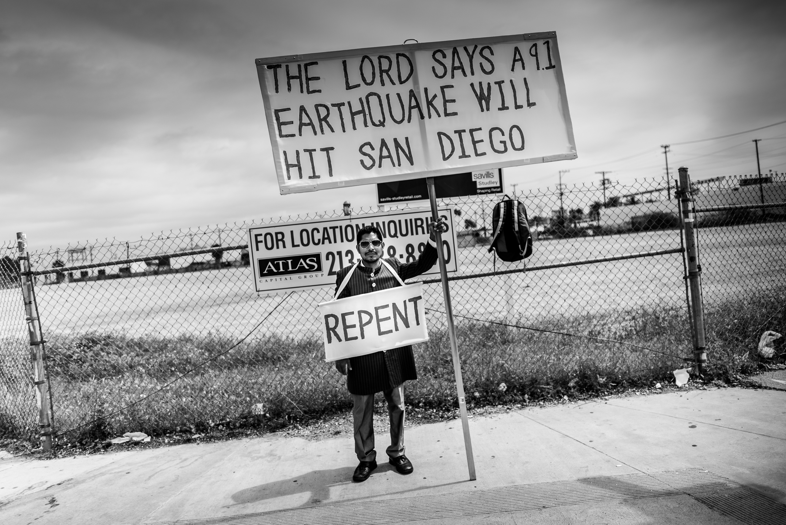 "a man stands on a street corner near Chinatown in Los Angeles. He holds a huge sign in a pole on which is painted, ""The Lord says a 9.1 earthquake will hit San Diego"". Around his neck is a rope holding a second, smaller sign with the word ""Repent"" on it."