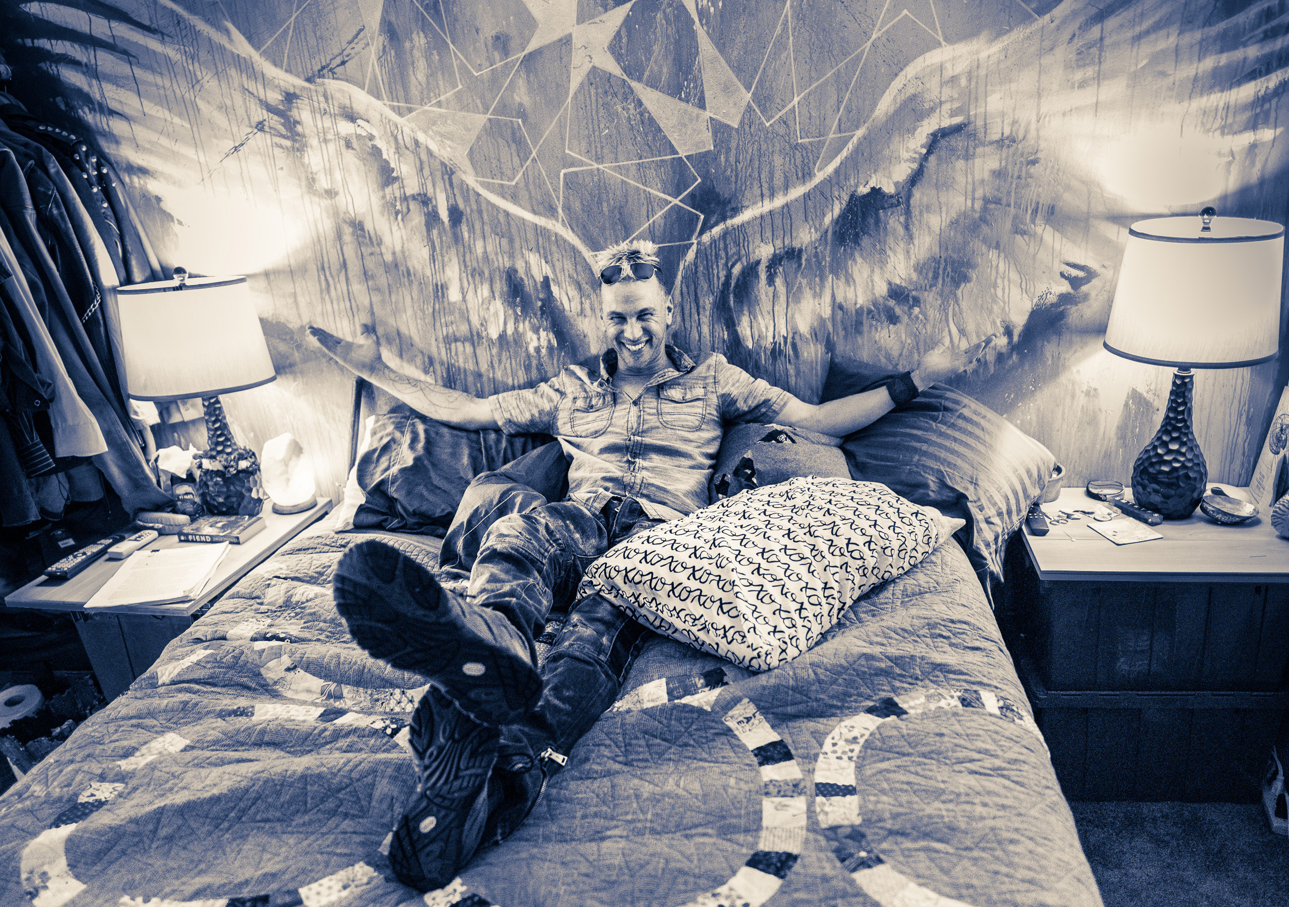 "Jason ""Hawke"" Hamilton lying on his bed in the upstairs loft of his  studio at the Brewery Arts Colony in Downtown Los Angeles. Behind him, as a sort of painted headboard, is a large pair of angel wings on the wall. Hamilton smiles and spreads his arms to fill the wings."