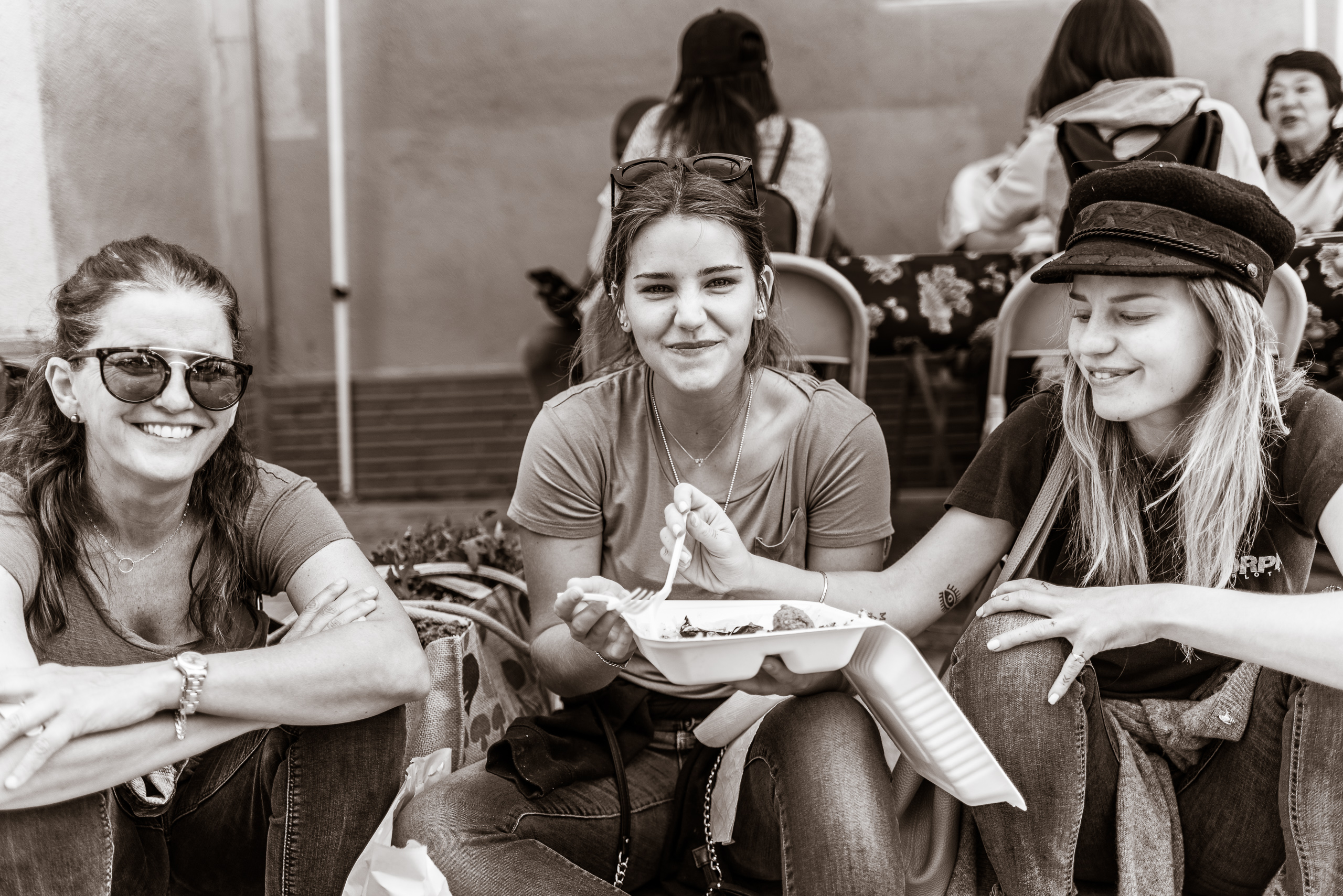 three women sit on a curb a share a freshly prepared meal at the Sunday Morning Hollywood Farmer's Market near the corner of  Ivar and Selma