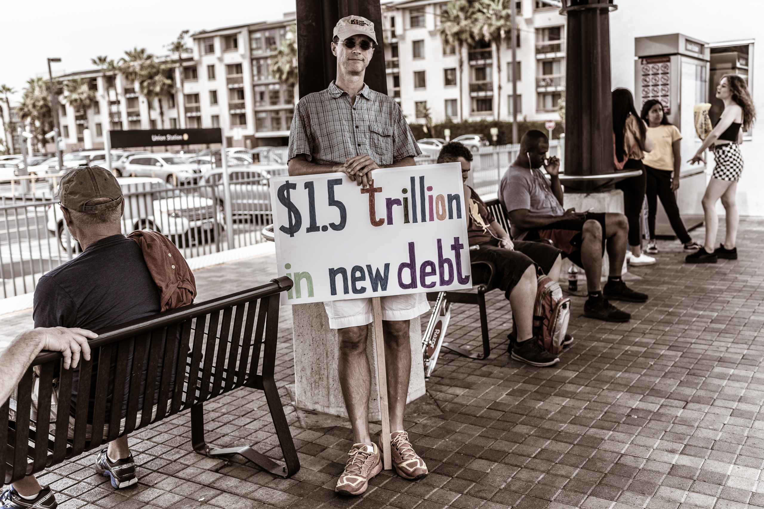 "a man stands on the Metro Gold Line Platform at Union Station holding a sign from a march he's just participated in. The sign reads, ""1.5 Trillion in New Debt"""