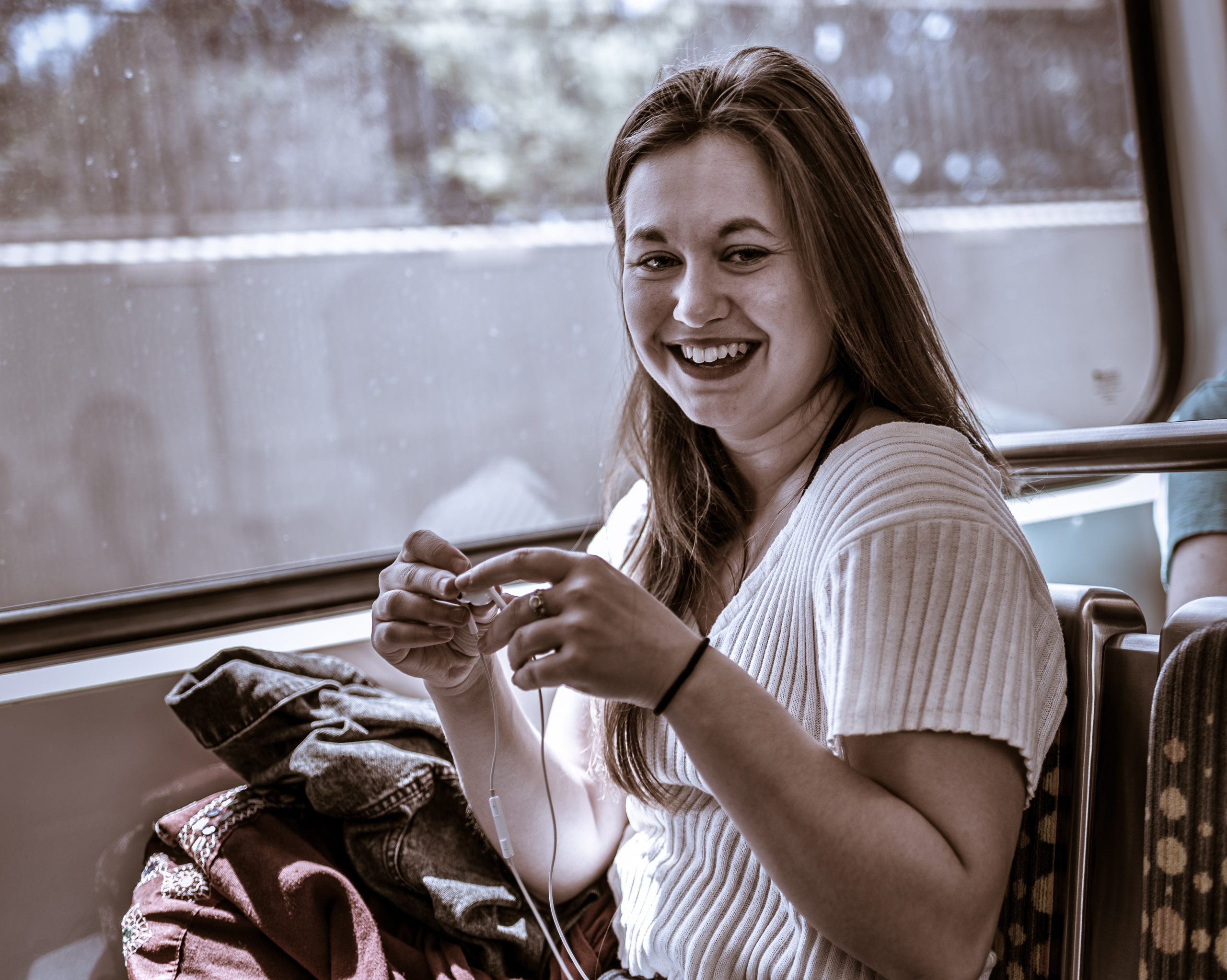 a photography student from Ithaca College spending a semester at ICLA (Ithaca College Los Angeles) rides the Metro Expo Line out to Santa Monica and then Venice where she's doing a video shoot today.  Here she smiles and plays with earbuds at the Expo Line's Exposition Park stop.