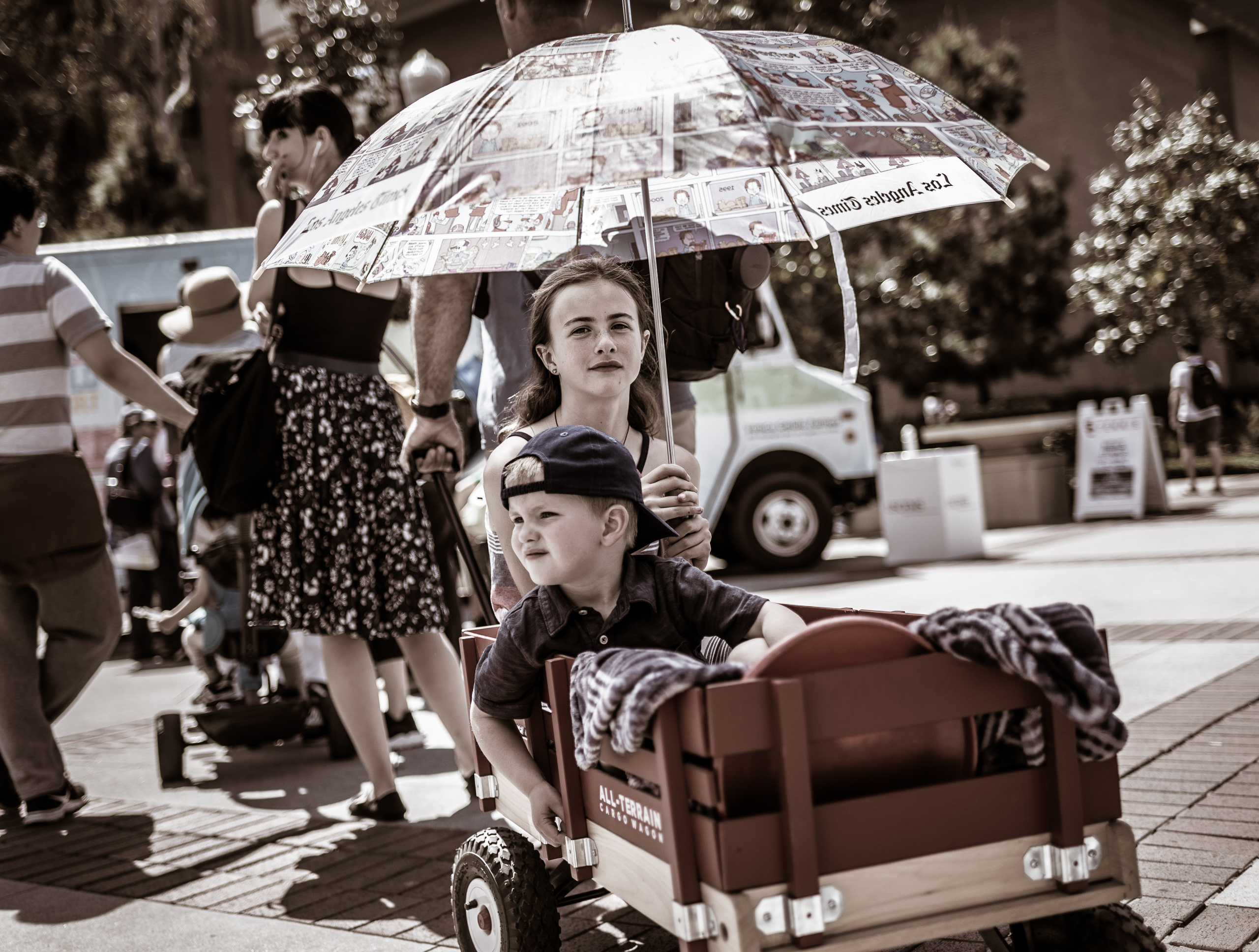 "A girl and her younger brother sit in a red wagon pulled toward a food truck by their dad. The girl holds a large ""Los Angeles Times"" umbrella. The girl looks at the camera. Her brother wears a baseball cap backwards and gazes off into the distance. The camera is low and on the level of the kids in the wagon."