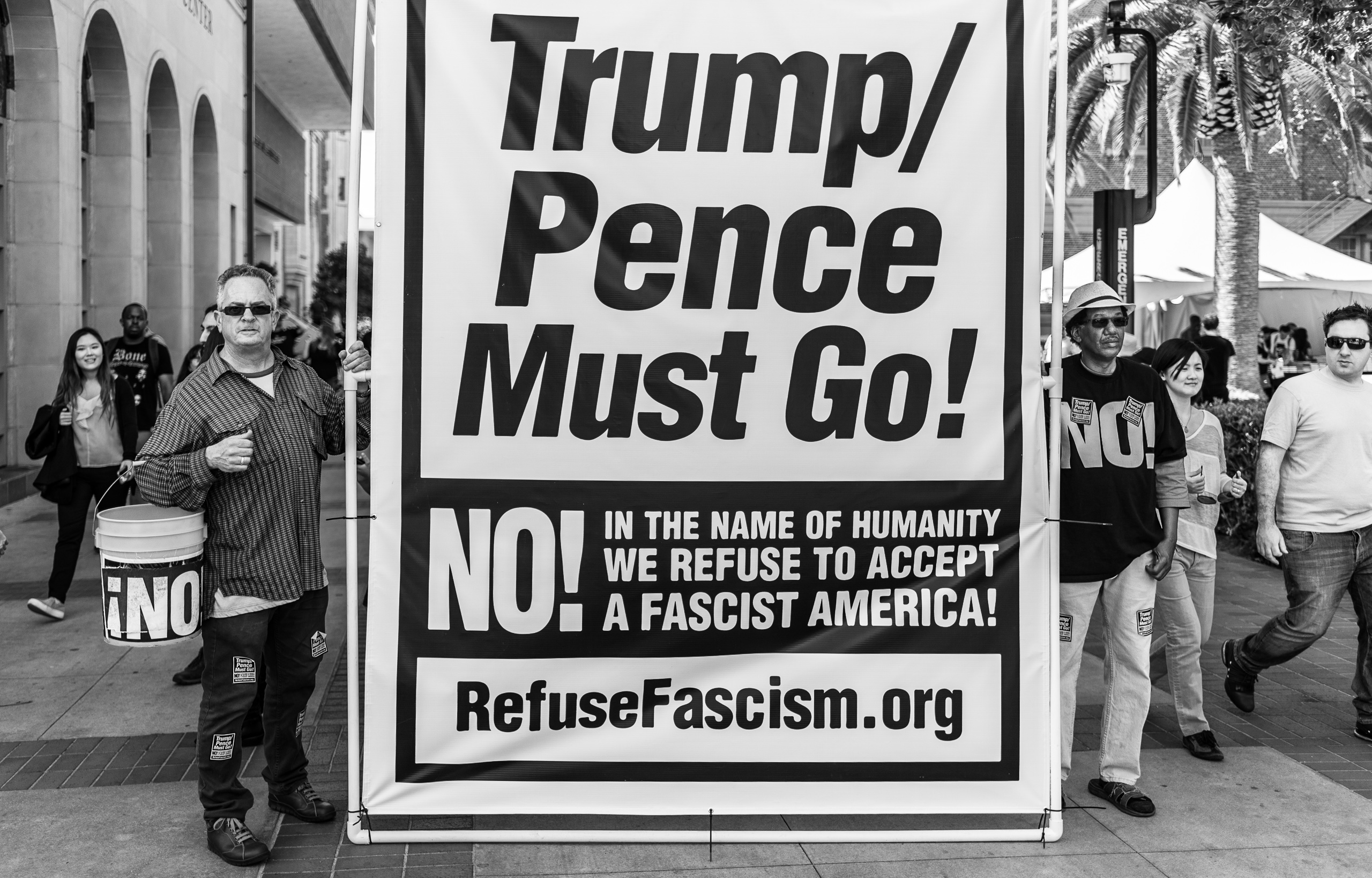 """Two men hold a large sign reading """"Trump / Pence Must Go! No! In the name of humanity we refuse to accept a fascist America! RefuseFascism.org"""