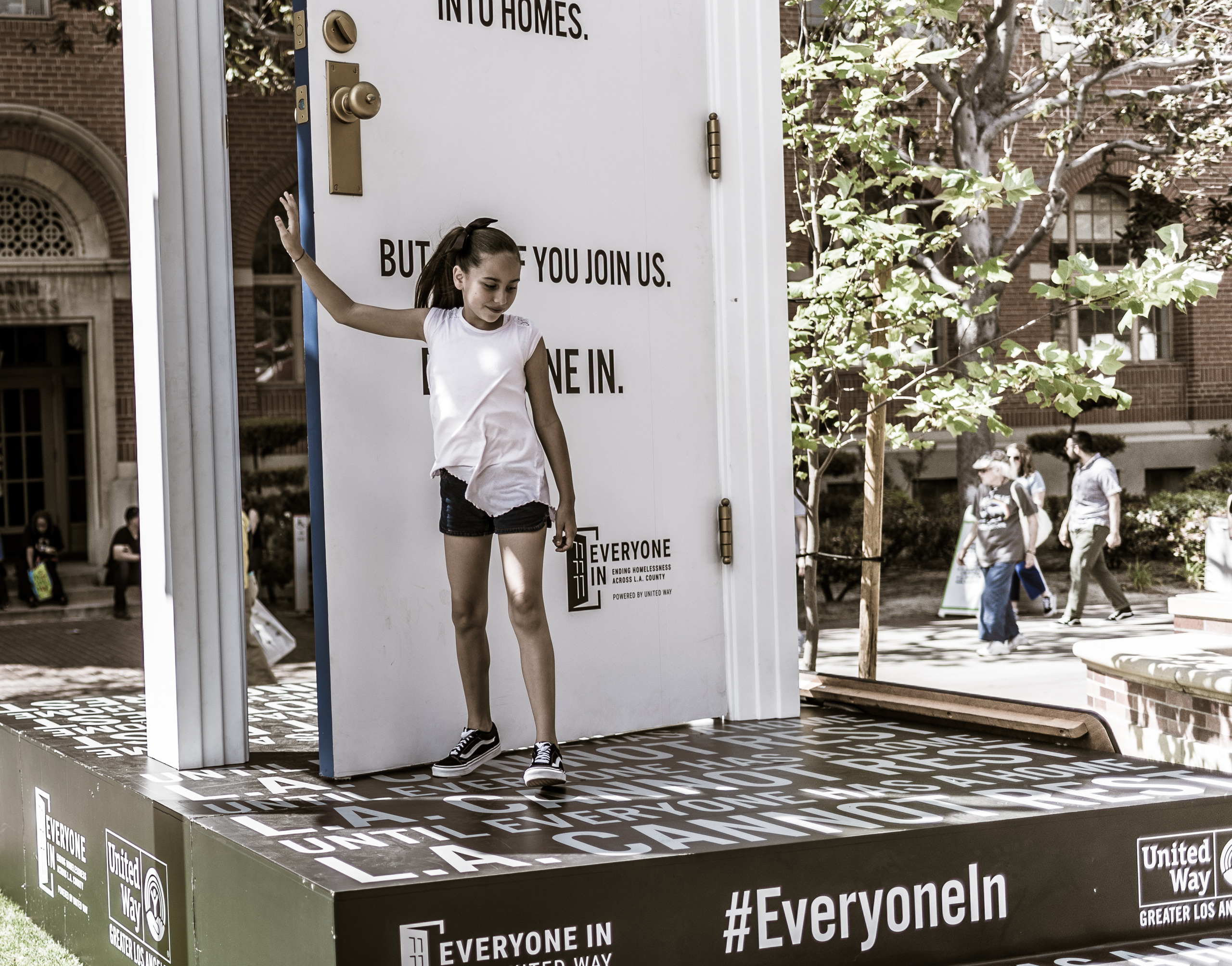 a young girl stands against a huge door with text on it. The text talks about the United Way's #EveryoneIn project to end homelessness in Los Angeles