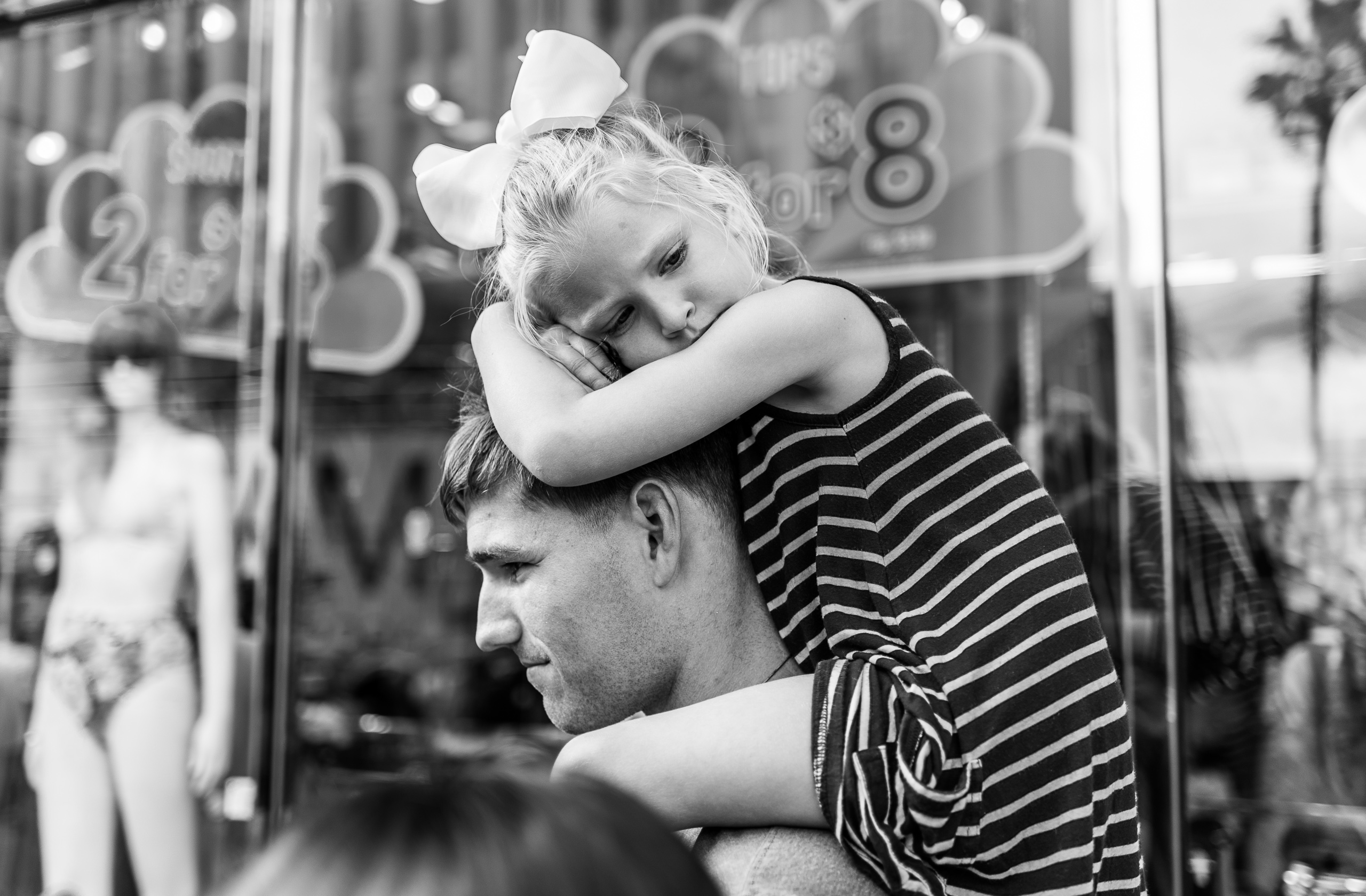 a young dad carries his daughter on his shoulders. She has her arms on top of his head and lays her head on his