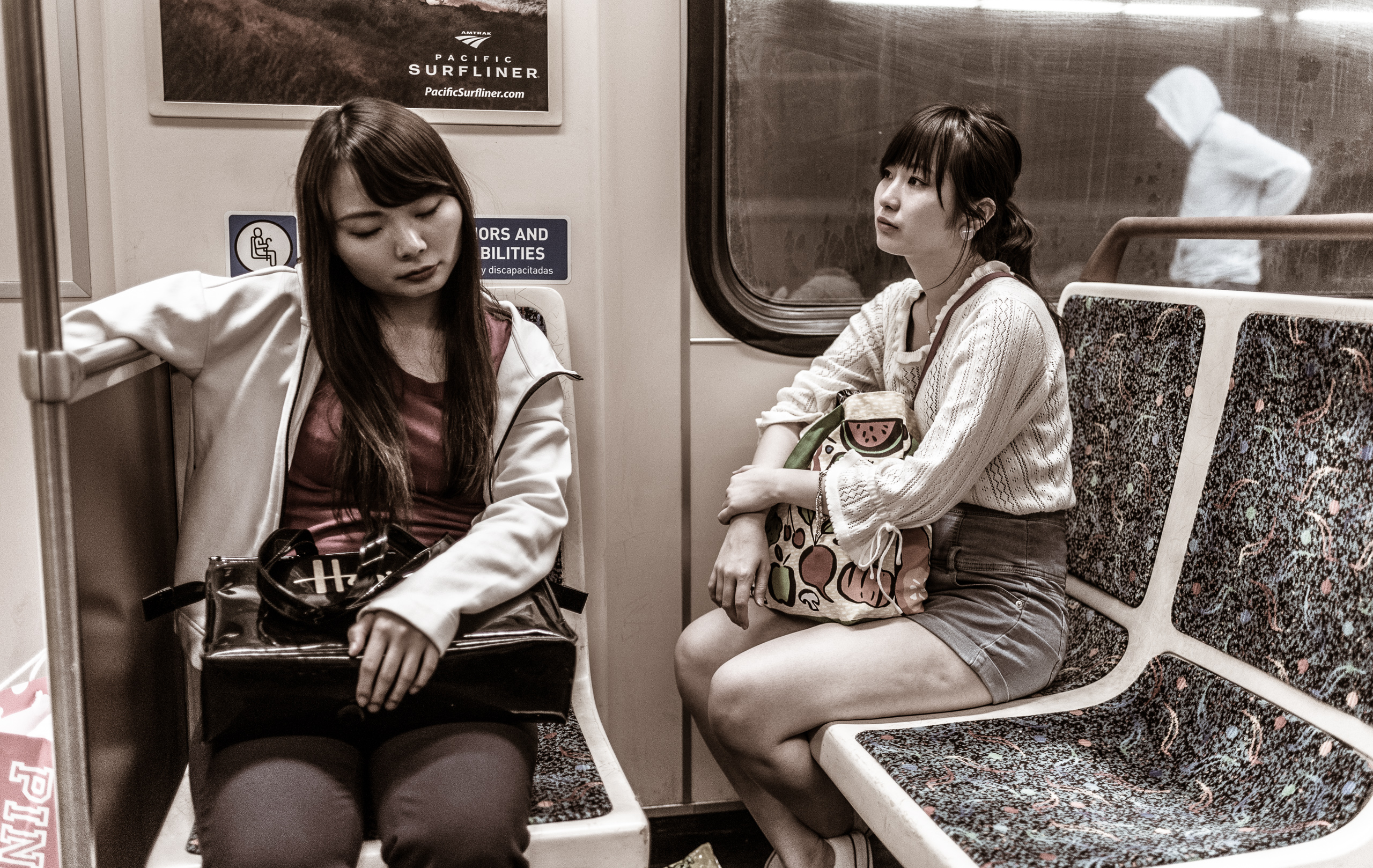 """two travelers sit in adjacent seats on the Metro Red Line bound for Union Station. One has her eyes closed and her head tilted. A """"Pink"""" Victoria's Secret bag is next to her. The other clutches a purse on her lap and stares into the distance. A portrait of tiredness."""