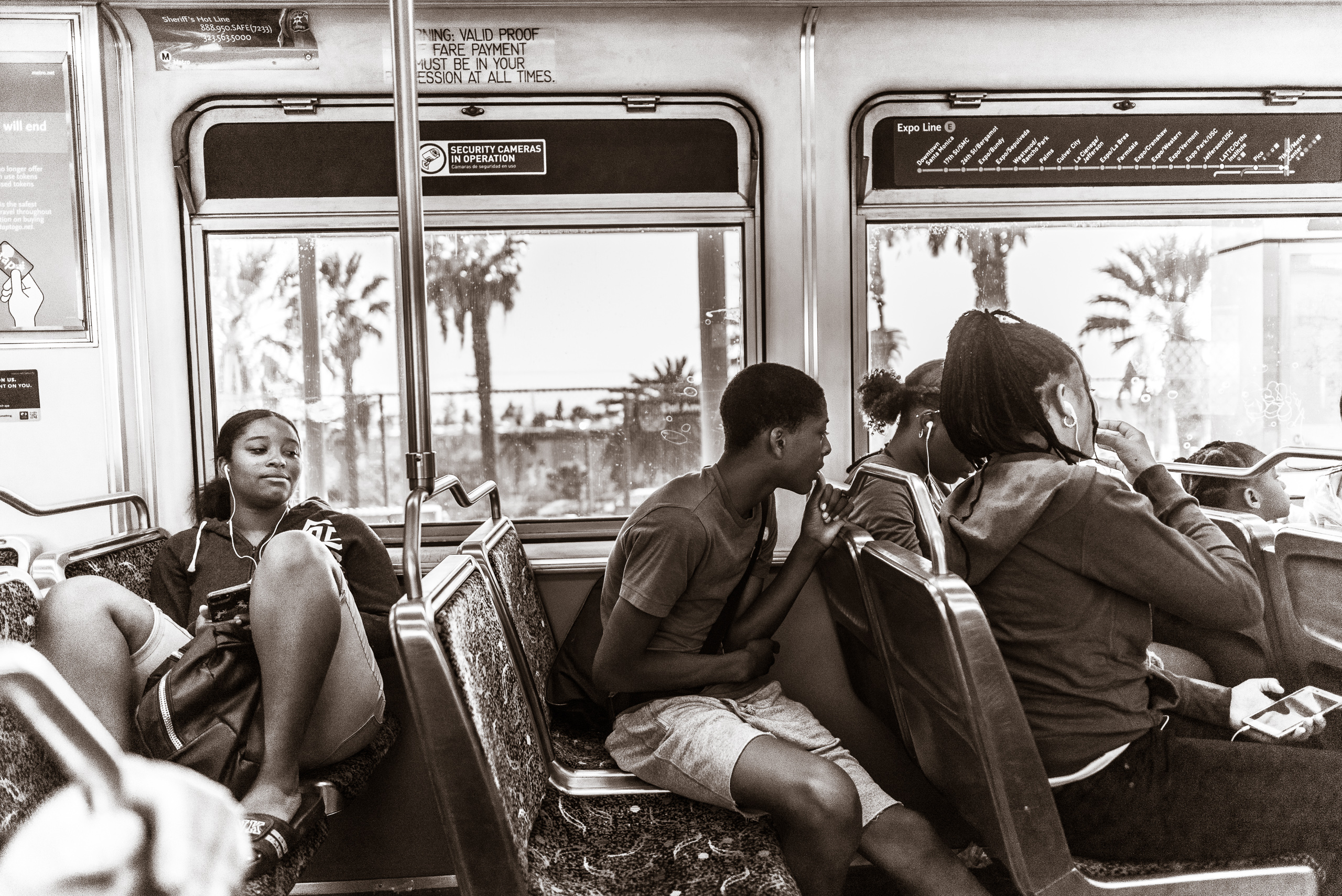 5 young people sit casually in 4 rows of seats on a Los Angeles Metro Blue Line light rail train heading North, from Long Beach to Los Angeles