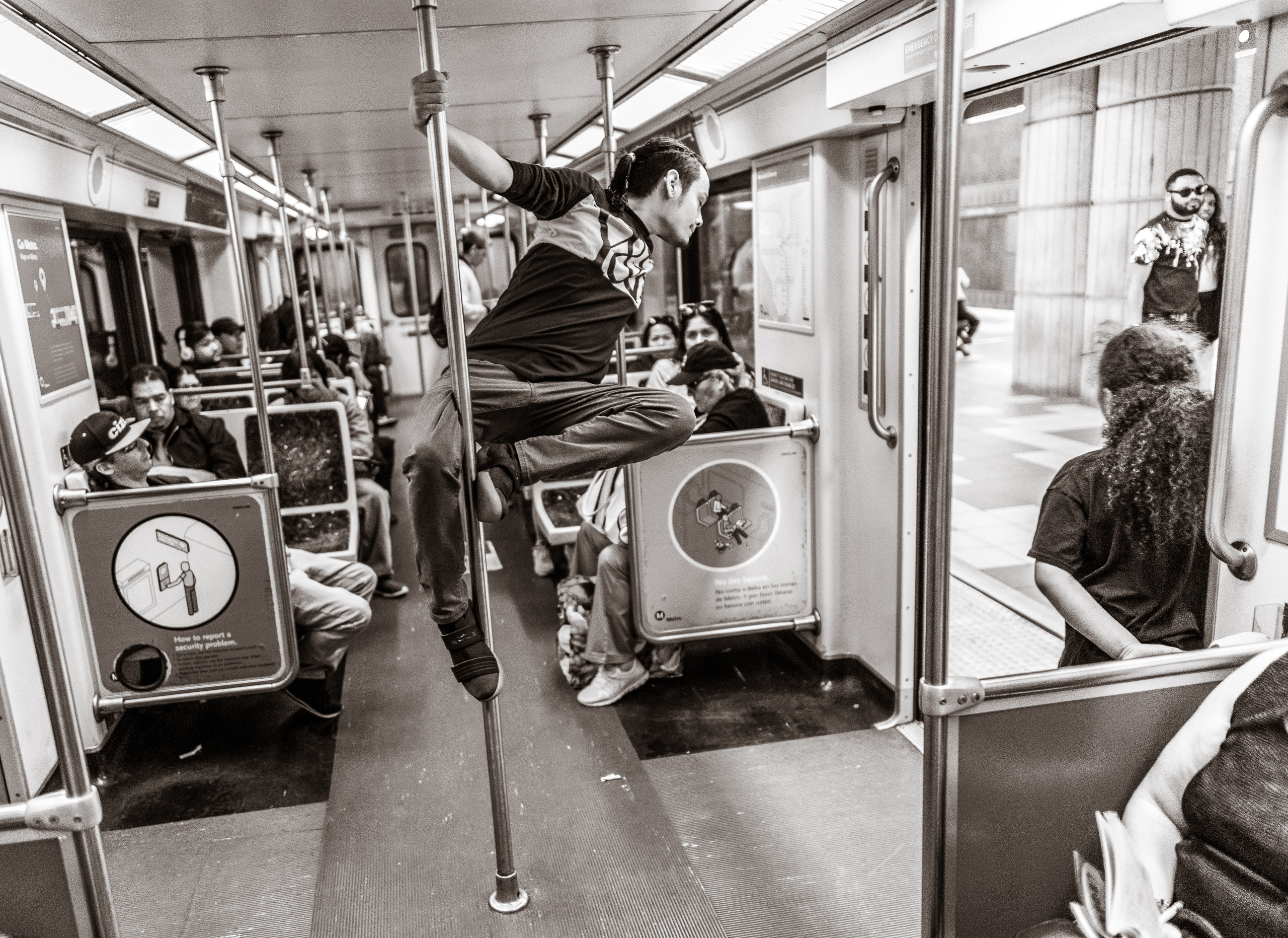 a guy does an impromptu dance performance using one of the vertical hand-hold poles on a Los Angeles Metro Red Line train car headed for North Hollywood on a Saturday afternoon