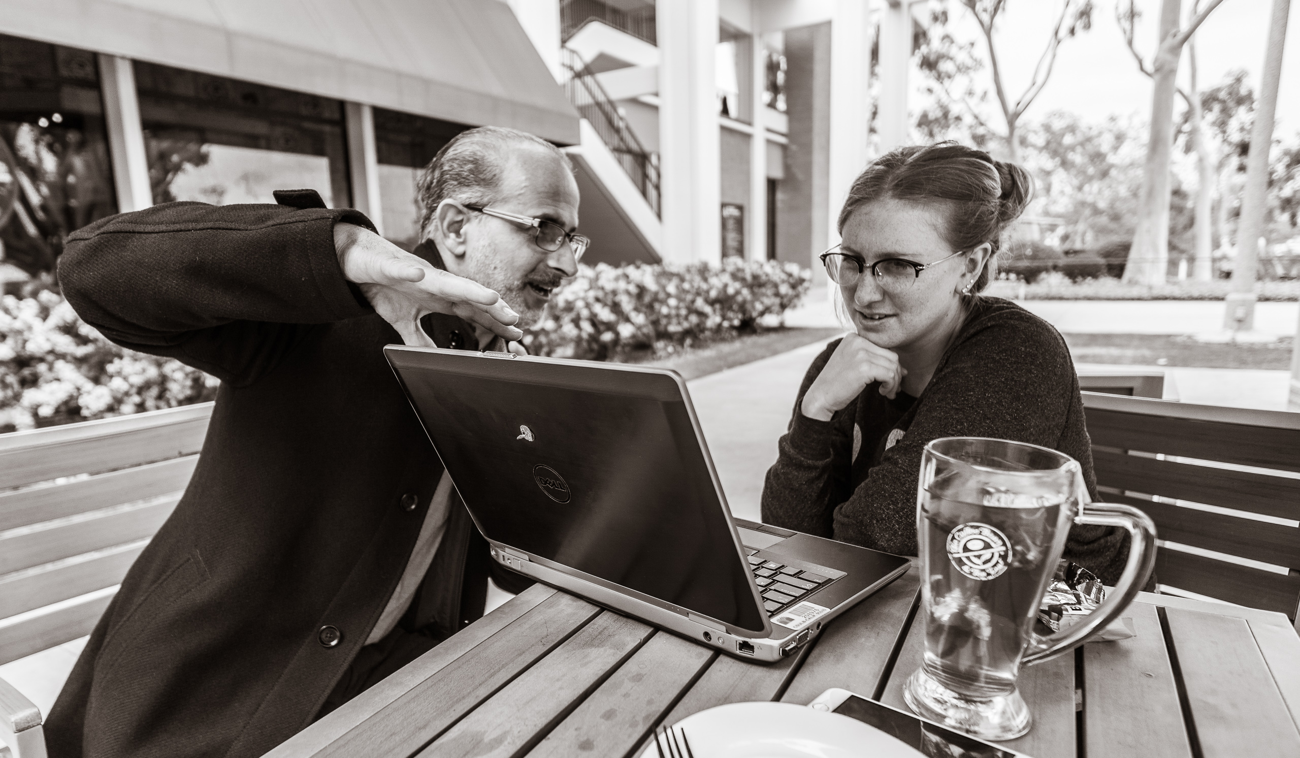 Dr. J and Julie Pavlacka sit at a table outside Coffee Bean & Tea Leaf at the University Student Union (USU) at Long Beach State University (LBSU / CSULB) and have an animated conversation over a laptop.