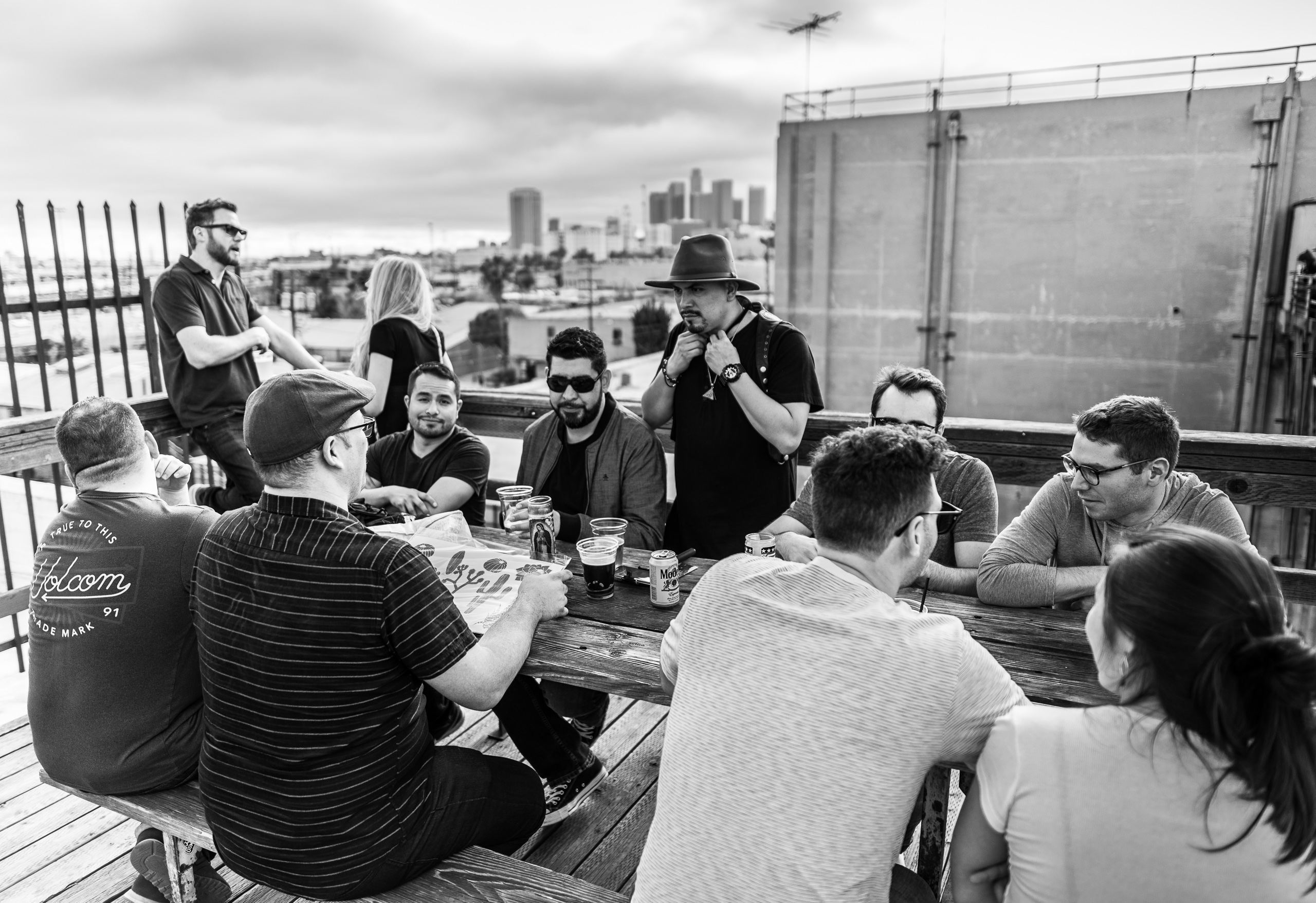 a group of people sit at a wooden table on the roof of one of the buildings at The Brewery Artist's Colony in Downtown Los Angeles. They drink beer and have an afternoon conversation. City hall and the other Downtown Los Angeles skyscrapers are off in the distance under a cloud-filled sky.