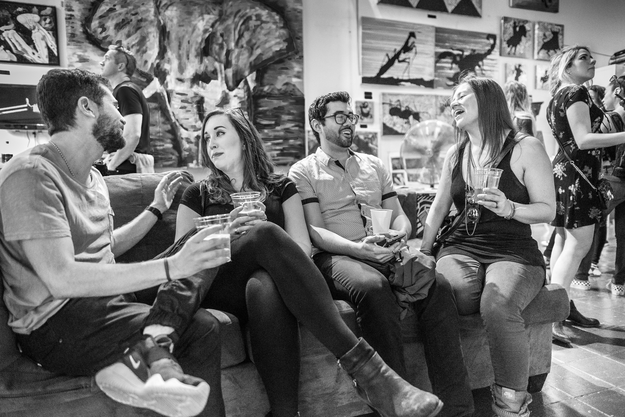 4 people sit on a couch, hold drinks, and converse, in an artist's loft at the Brewery Arts Complex in Downtown Los Angeles