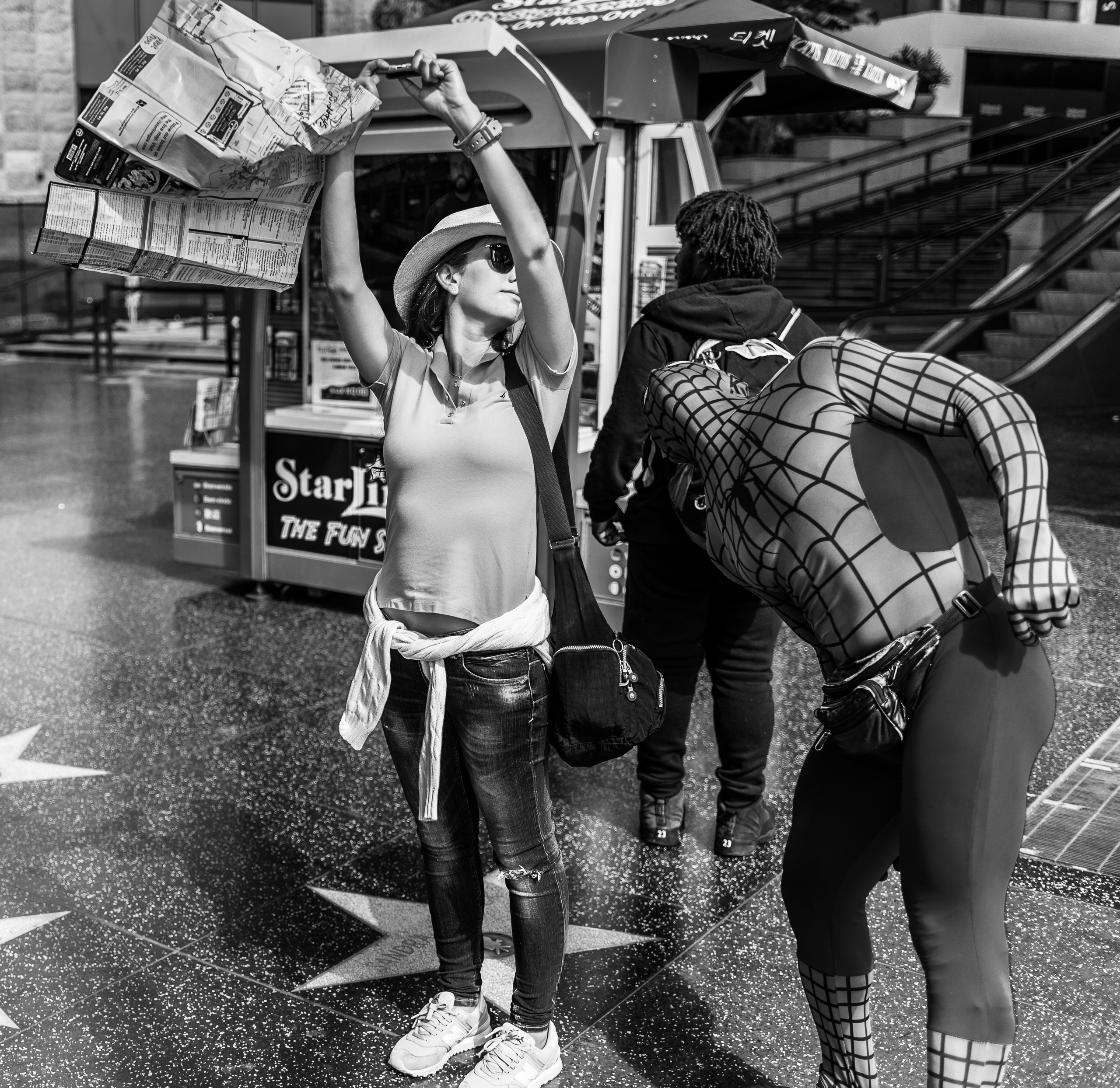 """a woman on the Hollywood Walk of Fame holds her cell phone high in the air to take a selfie, not realizing that """"Spiderman"""" is  photobombing her  from the side"""