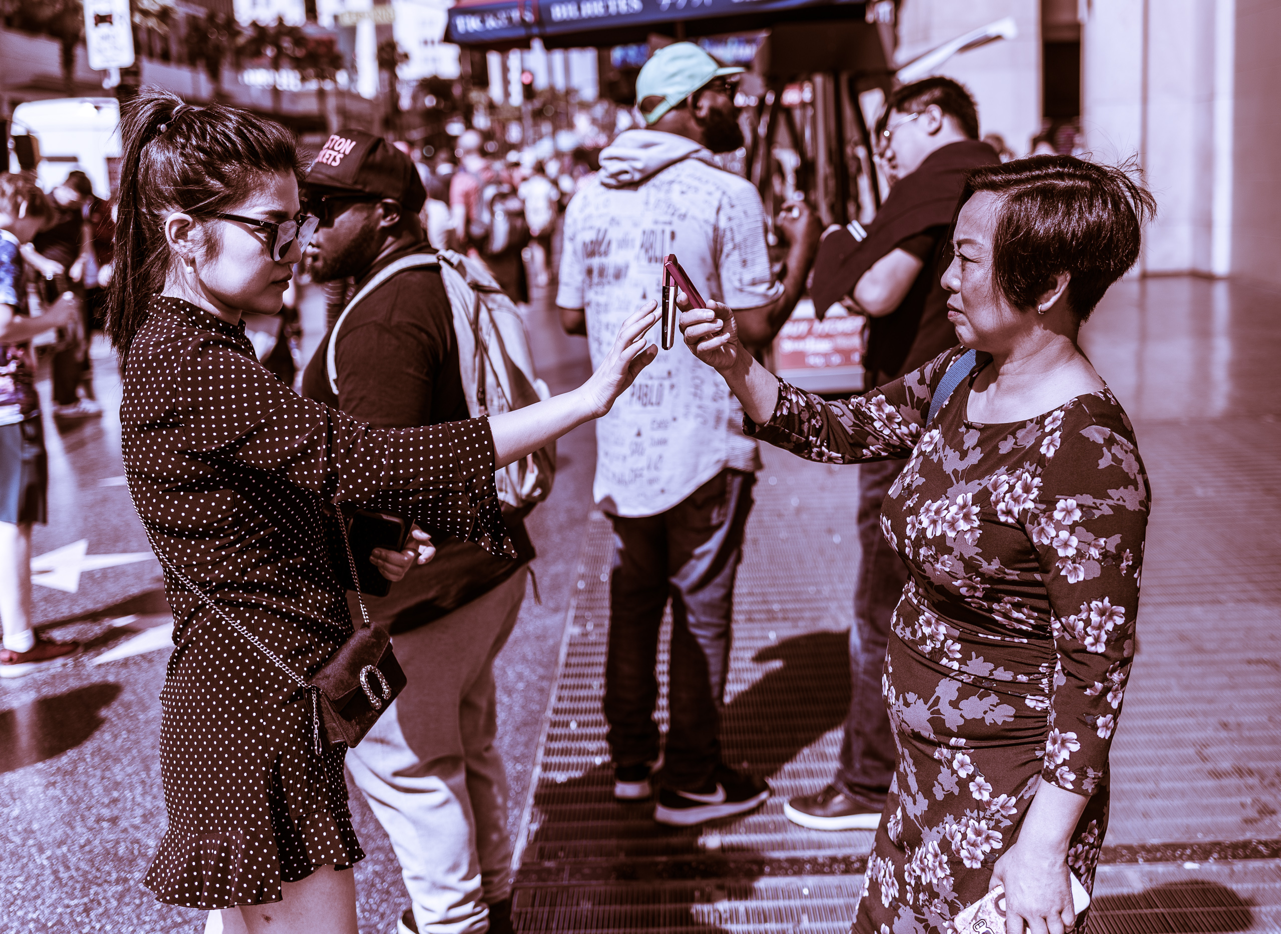 Two women stand on the Hollywood Walk of Fame and face each other. They have a cell phone between them. One holds the phone and the other makes a selection or touches something on the phone.