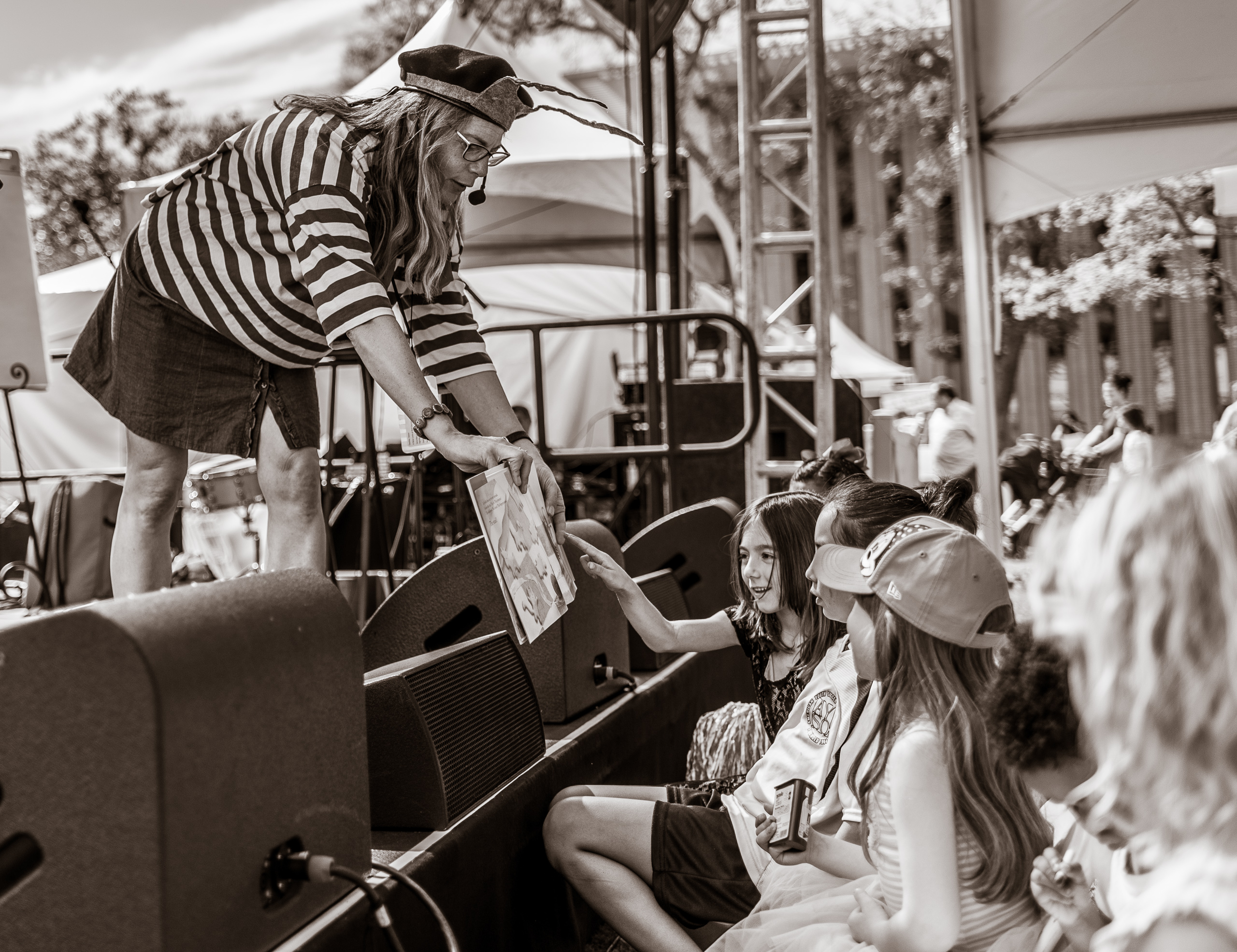 a woman on stage at the Los Angeles Times Festival of Books at the University of Southern California reads a children's book to the audience. She has some of the kids in the front row press on a special item on one of the pages of the book