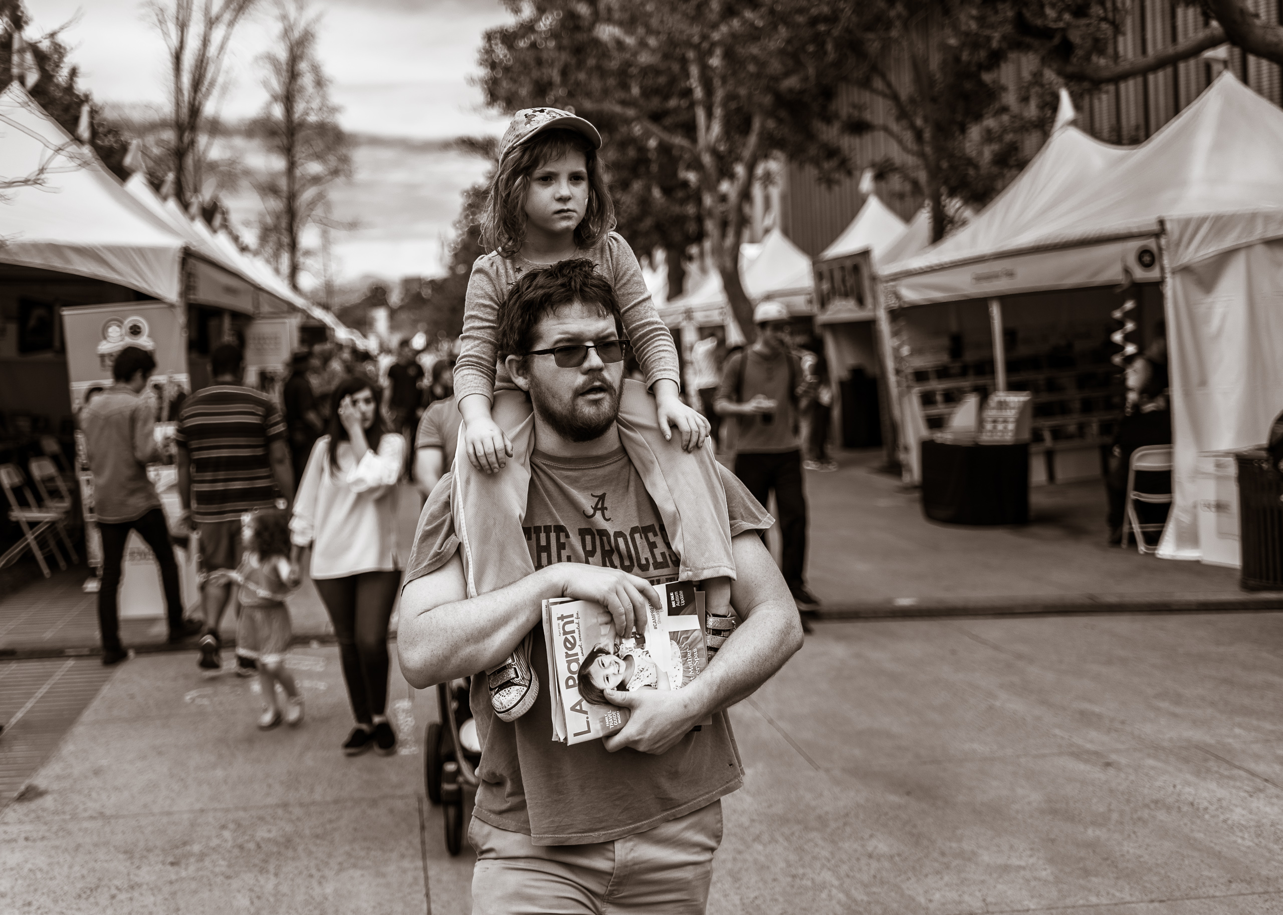 "a man carrys his young daughter on his shoulders as the walk through the booths at the LA Times Festival of Books at USC. He wears a t-shirt that reads ""The Process"" and her carries a stack of magazines in front of him, the top magazine's title being ""LA Parent"". His daughter wears a cap and rids calmly on his shoulders with her hands resting on her knees."