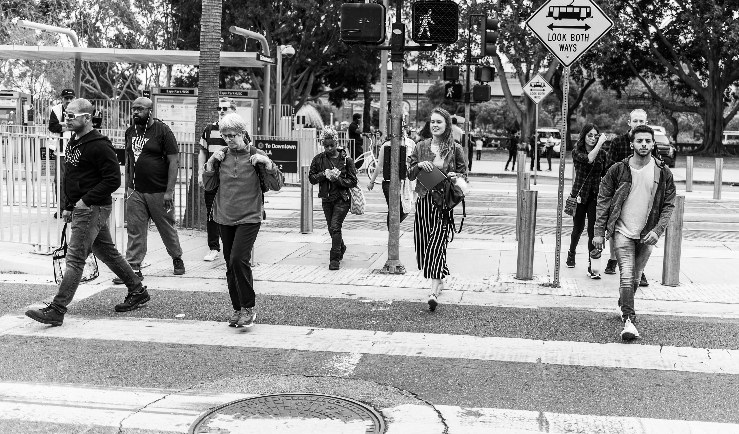 people crossing Exposition Blvd from The Museums and Metro toward the campus of USC and the Festival of Books